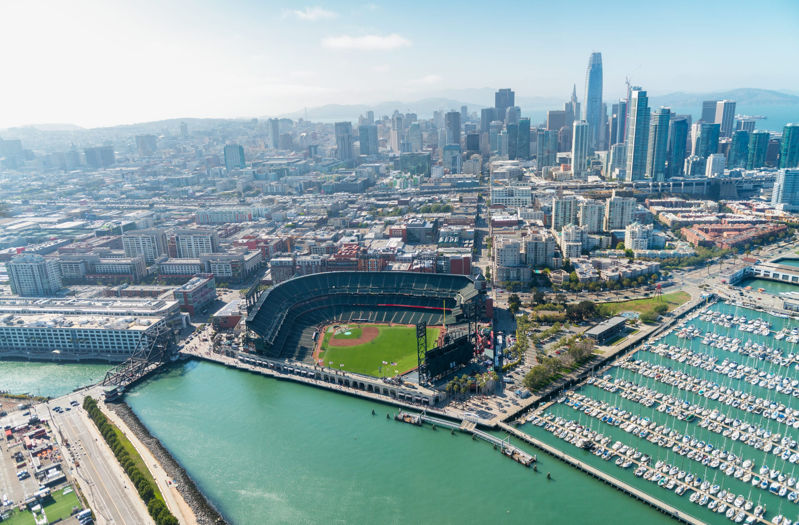 Aerial view of Oracle Park and the San Francisco skyline on a sunny day.