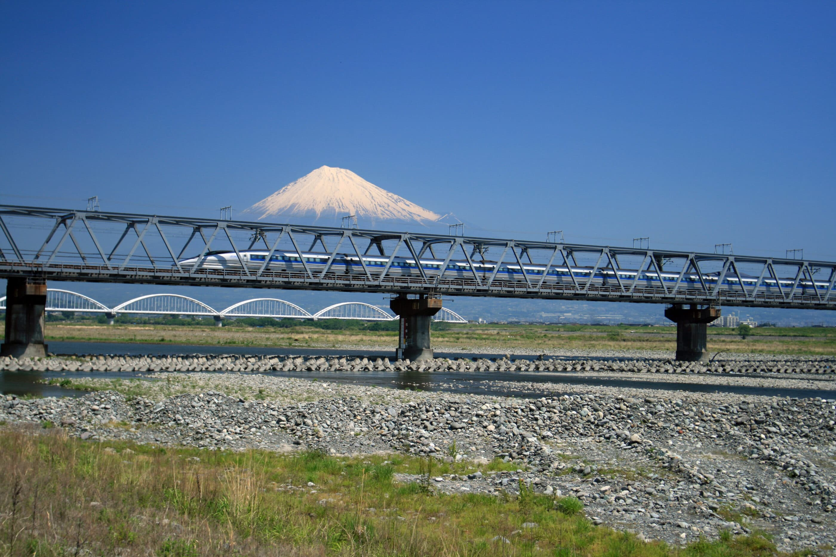A shinkansen bullet train passing by Mt. Fuji