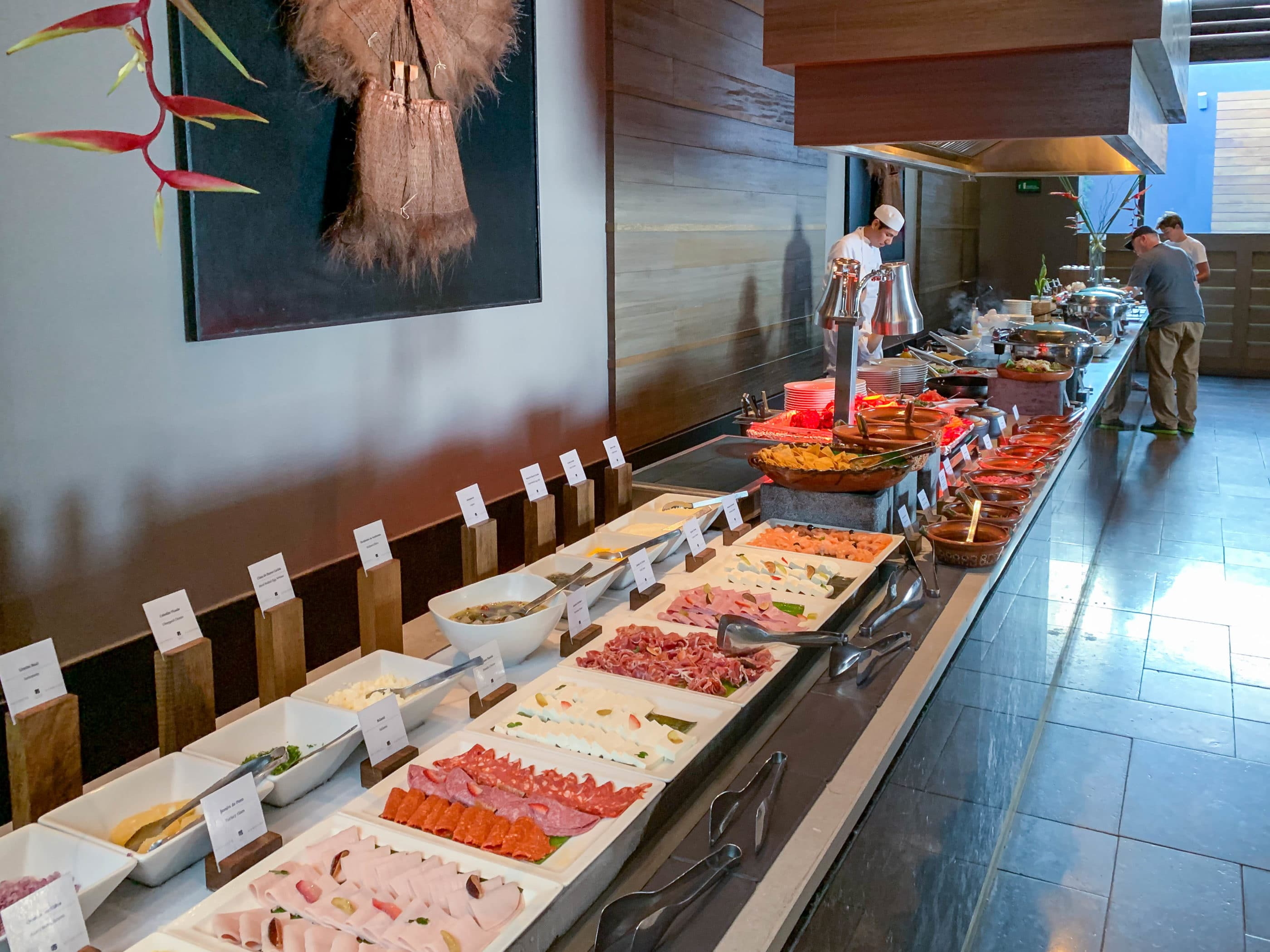 Part of the Nizuc breakfast buffet counter with cold cuts and a chef making pancakes.