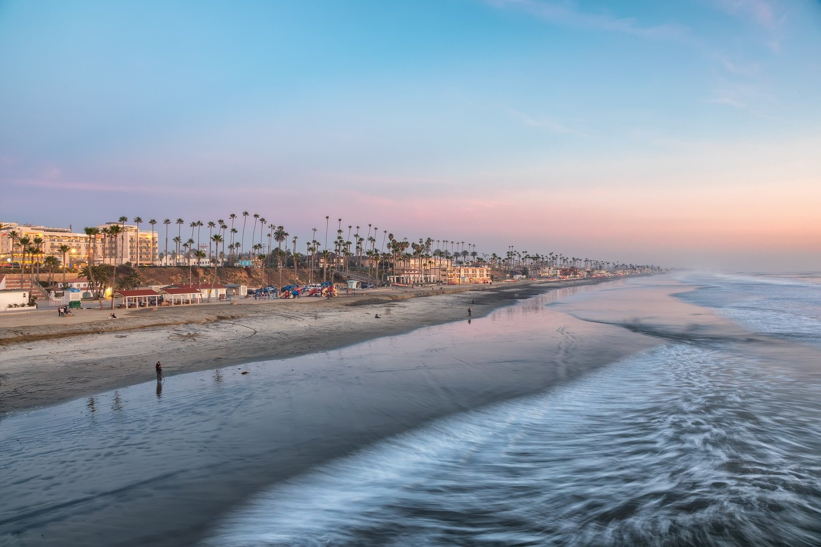 View of the Oceanside, CA beach from the pier at sunset.
