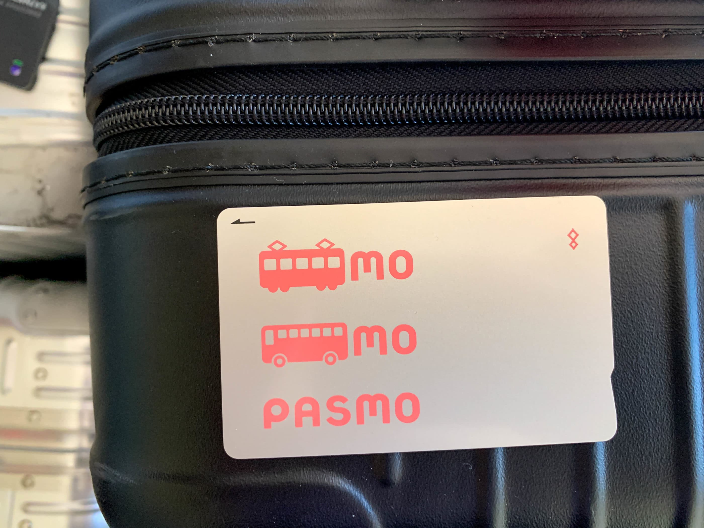 A Pasmo card sitting on top of a black suitcase