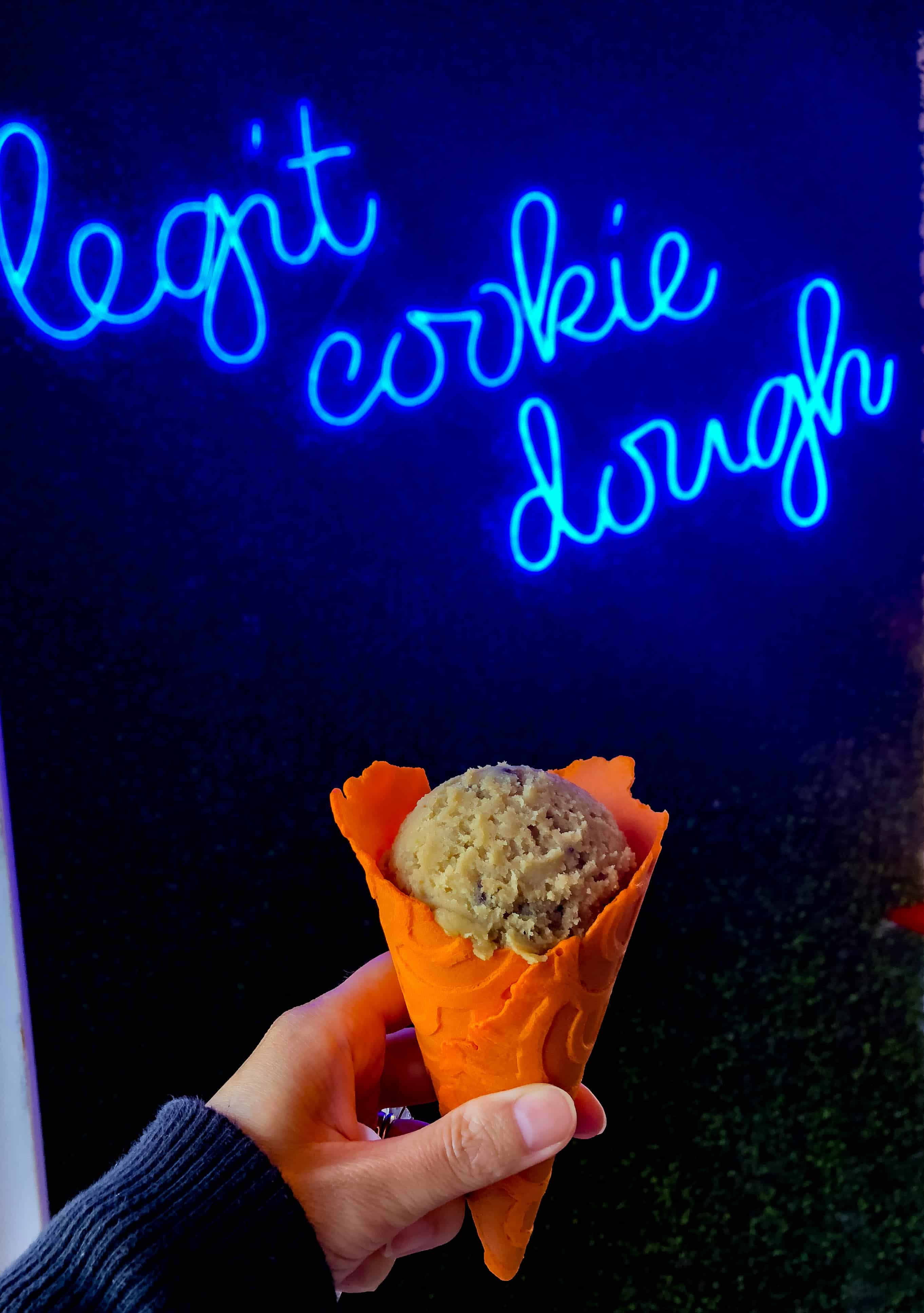 A cookie dough cone from Doughp in front of a neon sign at Pier 39 San Francisco