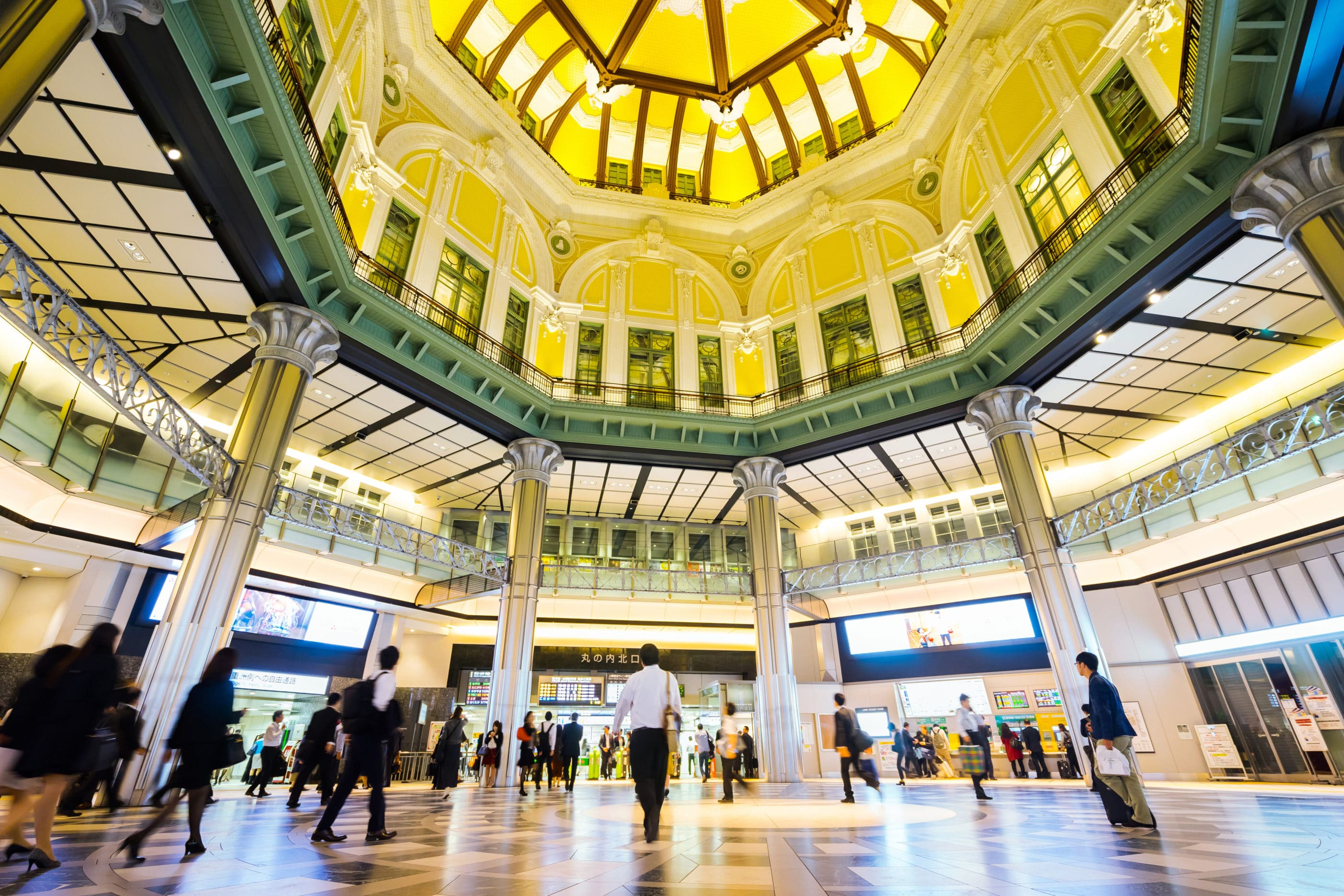 Looking up at the Tokyo Station green and yellow atrium