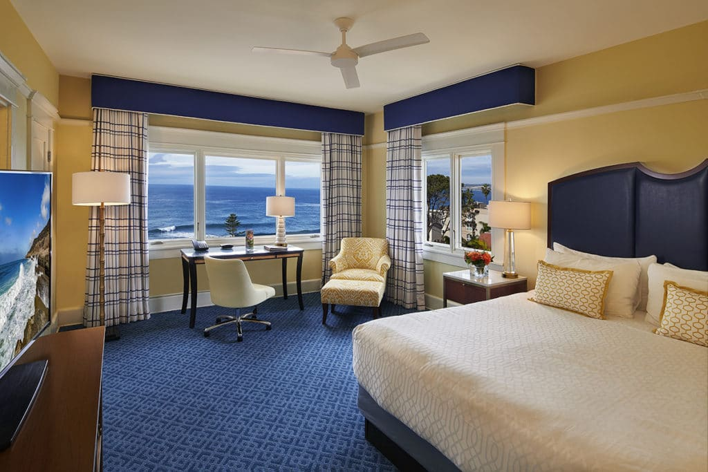Interior of Ocean View King room features blue carpet and coastal accents.