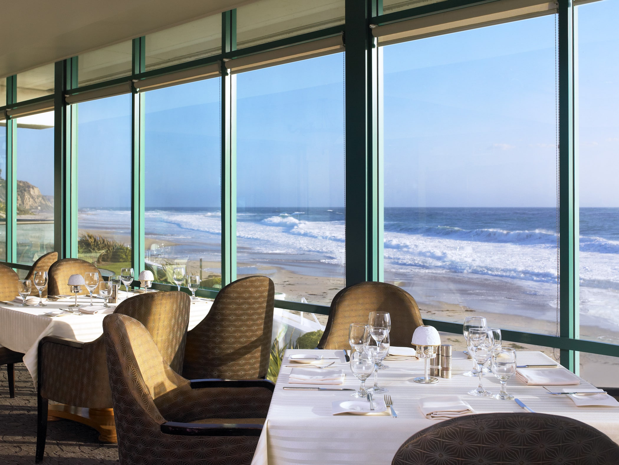 Floor-to-ceiling windows at Monarch Bay Club showcase the beachside location and ocean.