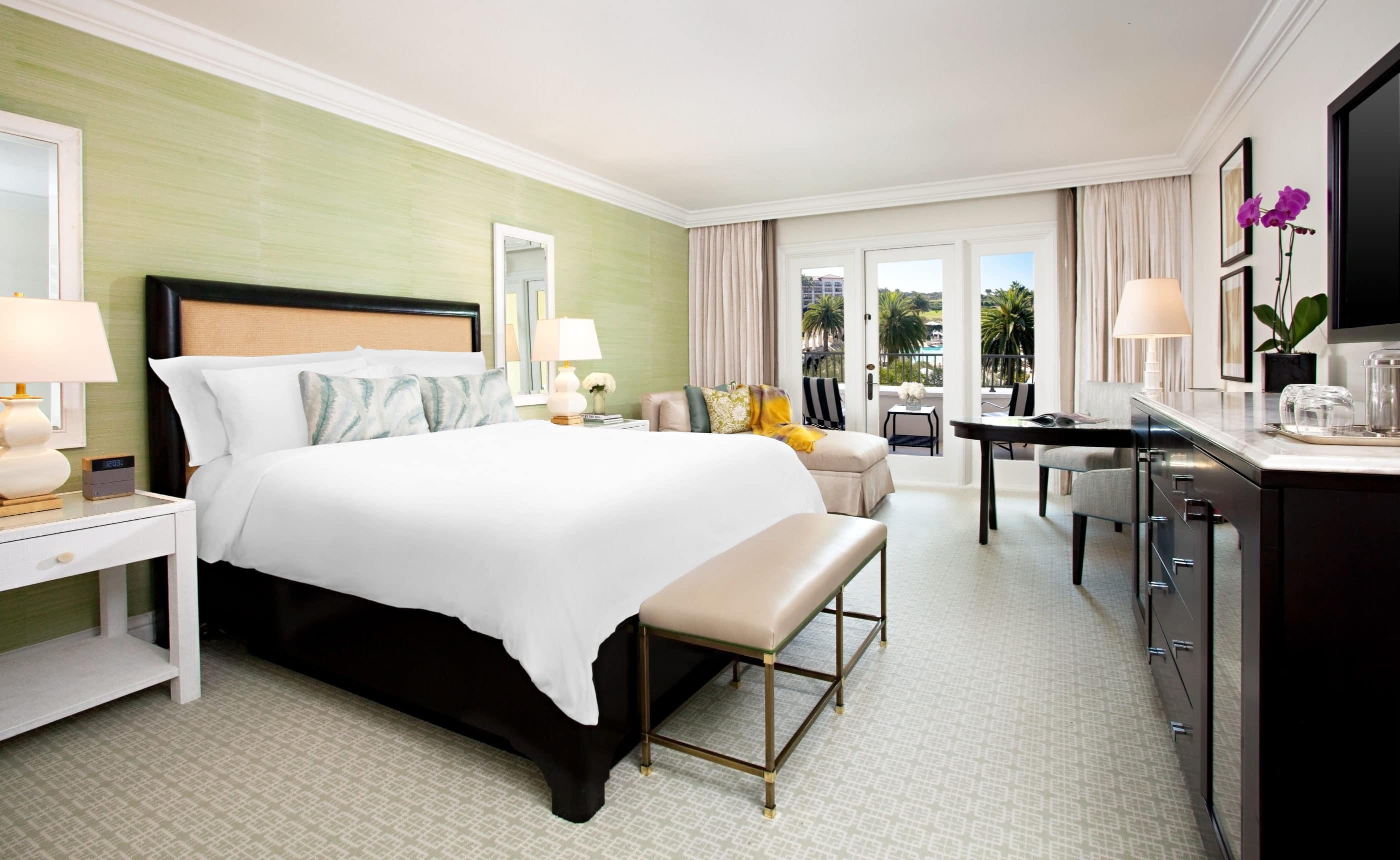 The interior of a Signature King room at Monarch beach resort with crisp white sheets, and coastal colored accents.