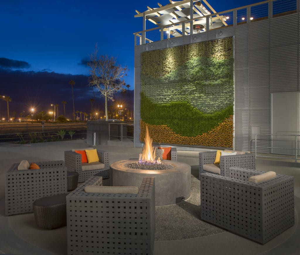 Outdoor fire pit lit up at night and surrounded by lounge chairs