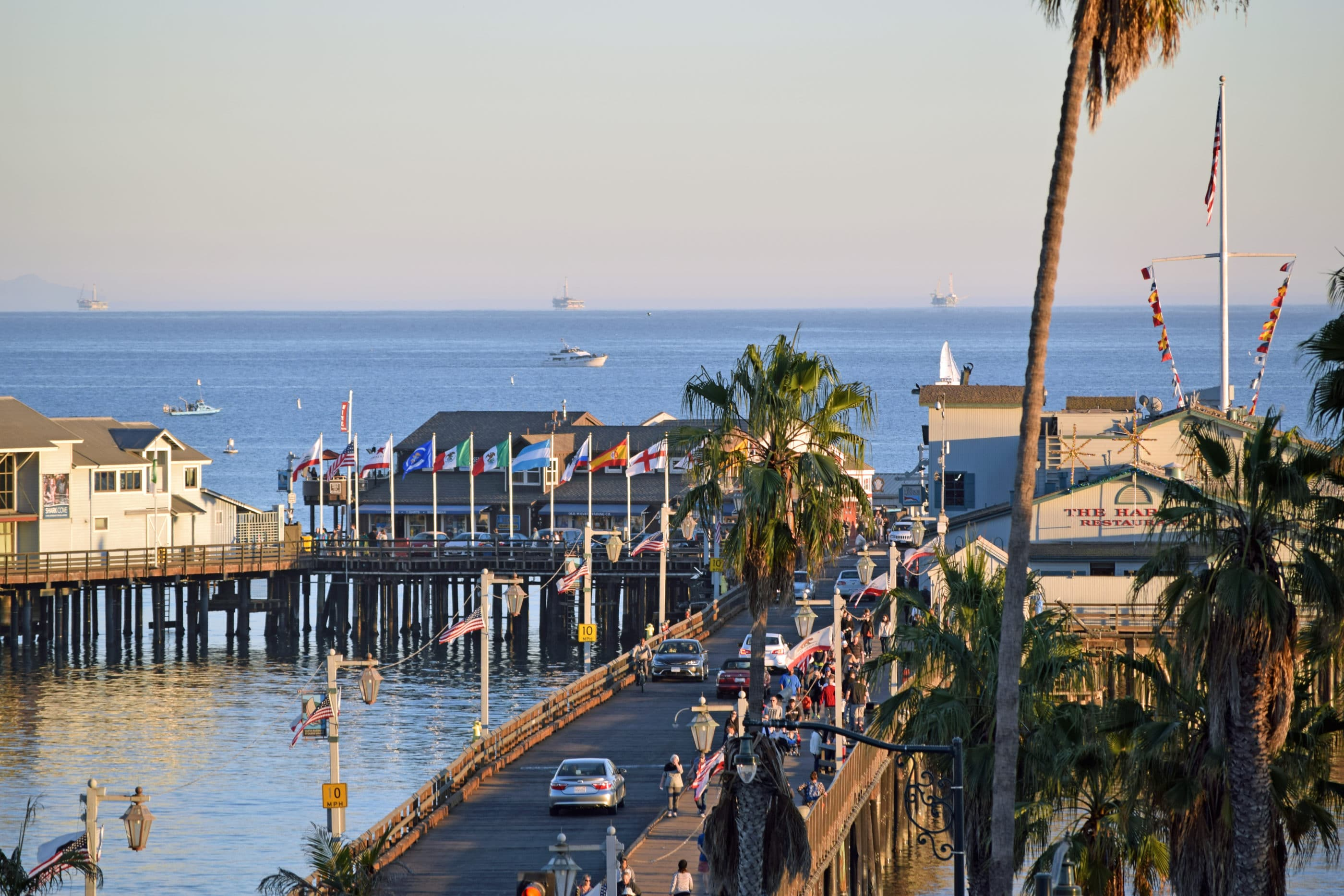 An aerial shot of cars driving down the Stearns Wharf pier in Santa Barbara.