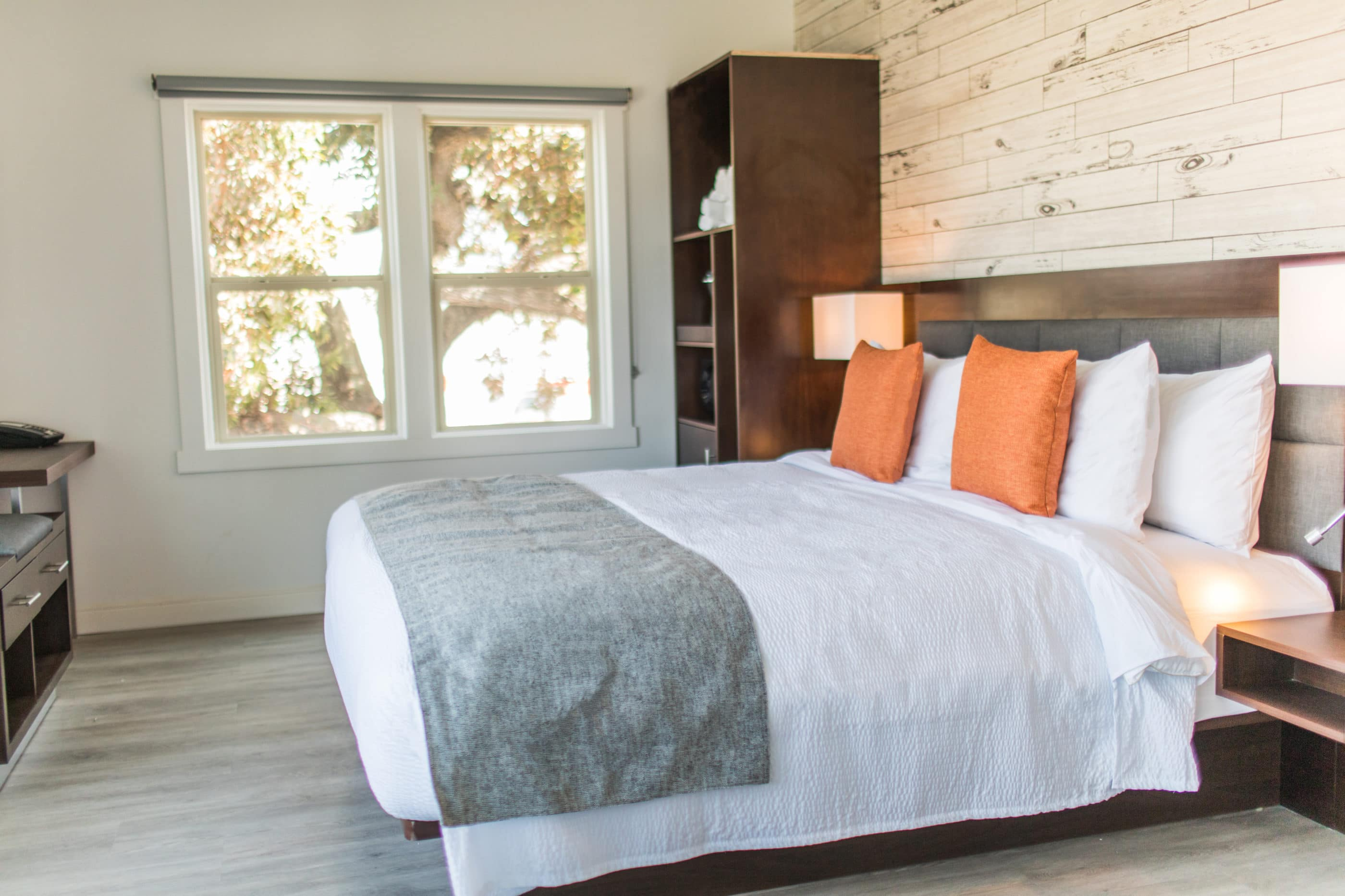 Guestroom with contemporary decor (bed with crisp white sheets, orange throw pillows and a grey blanket across the edge) at The Fin Oceanside