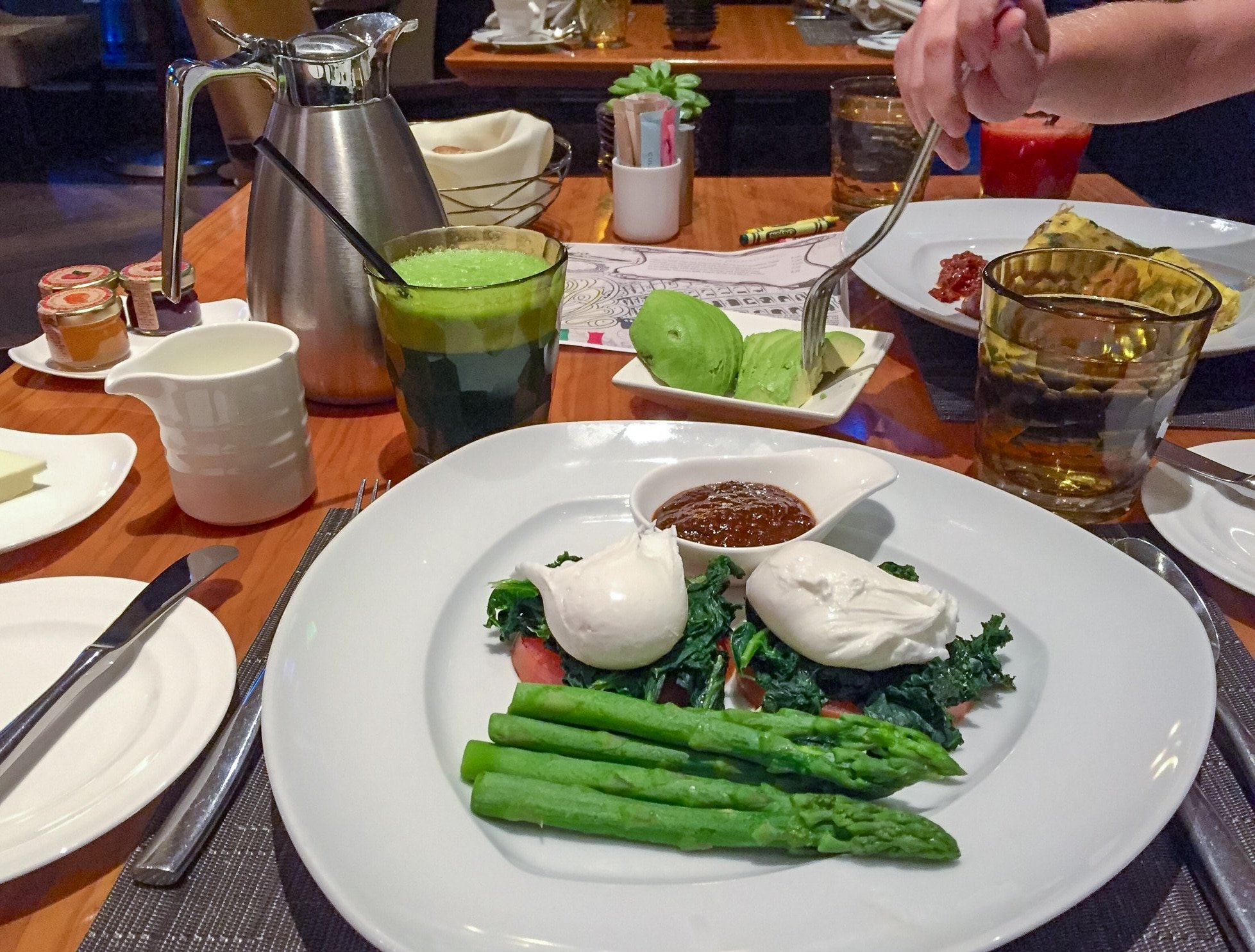 Poached eggs, steamed asparagus, and other vegetables on a plate at Culina as part of a healthy breakfast spread.