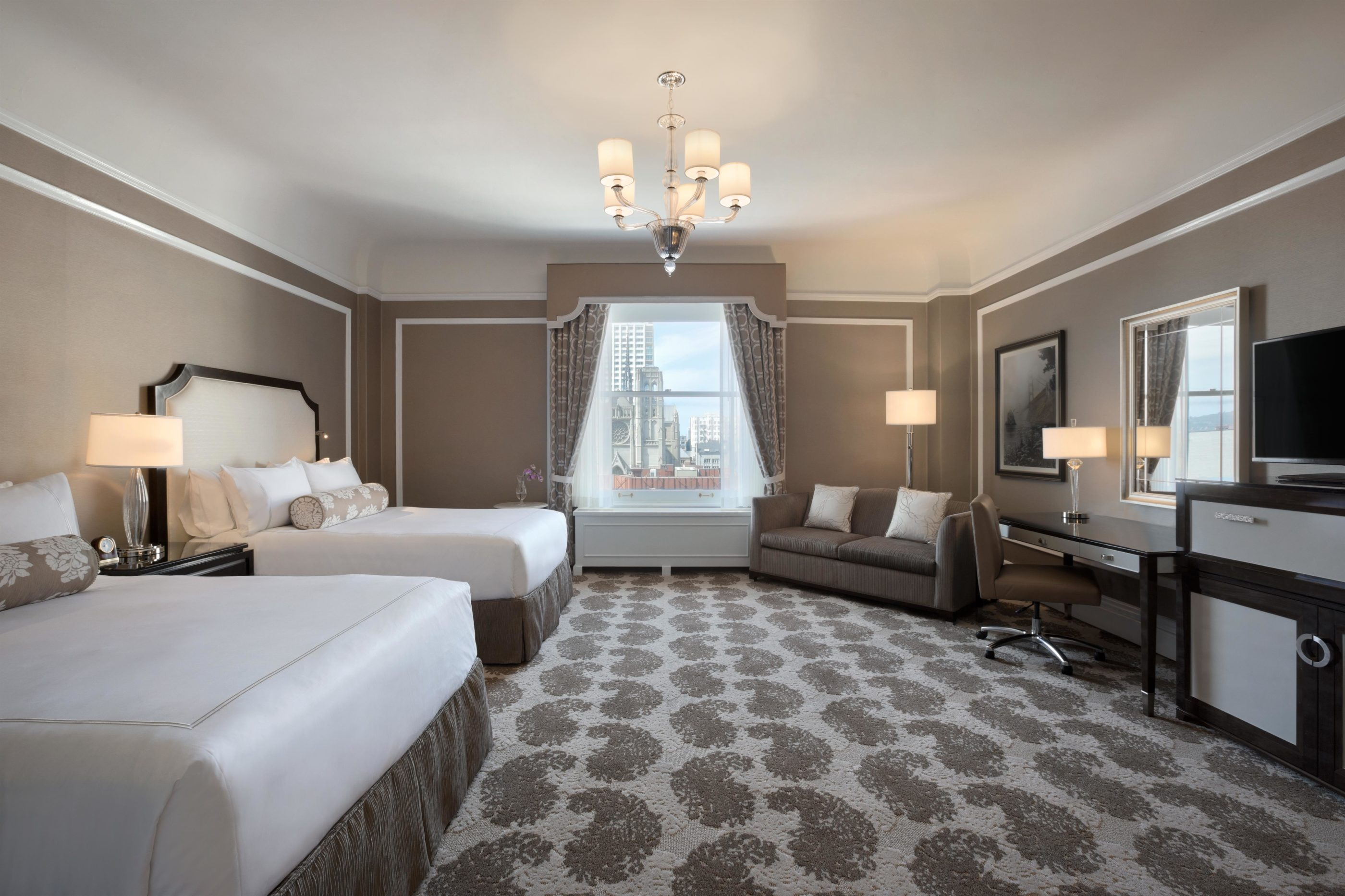 The interior of a Fairmont Queen/Queen room with taupe walls, dark woods and white accents.
