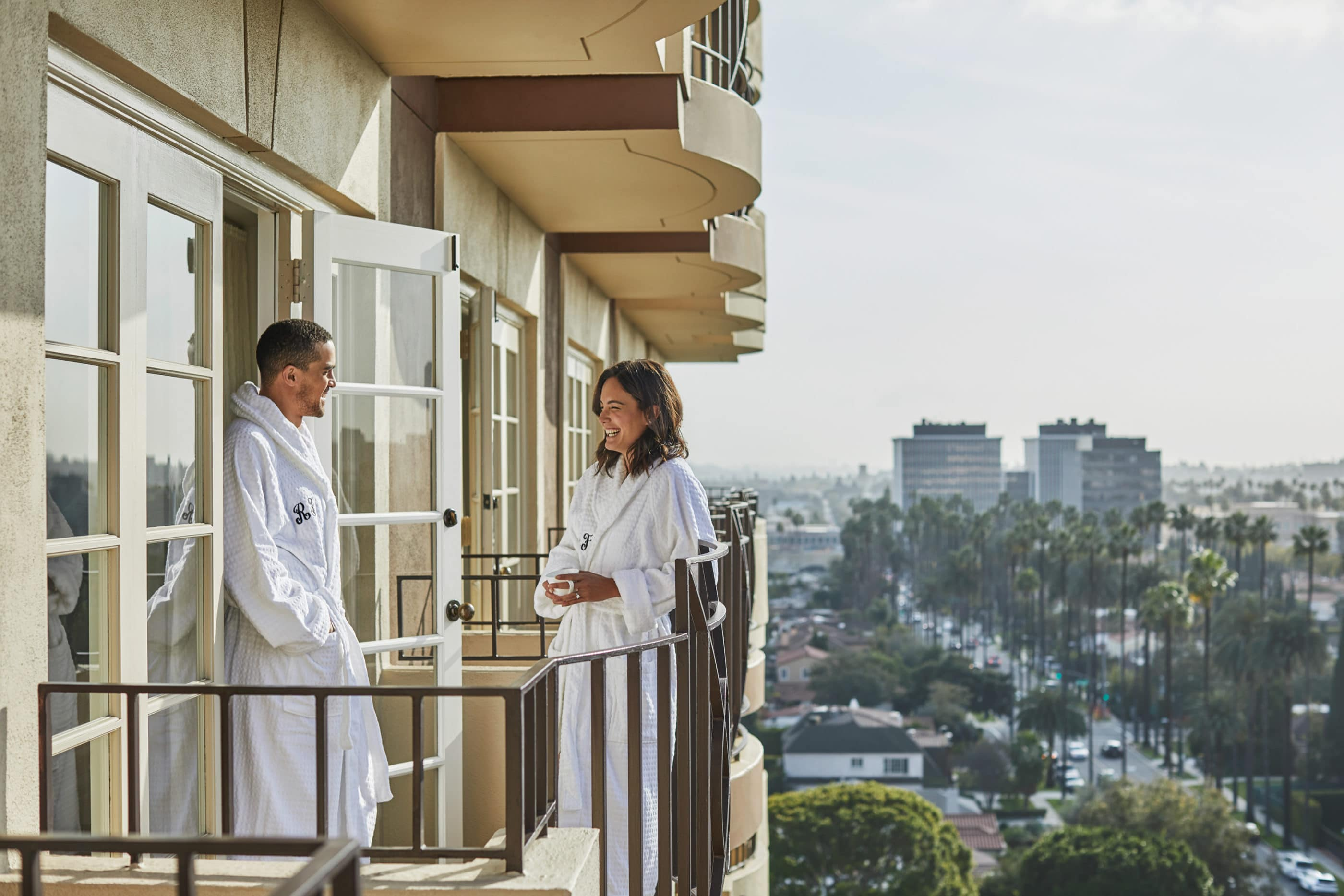 A couple in bathrobes chats while standing on a hotel balcony, with views of Los Angeles in the background.