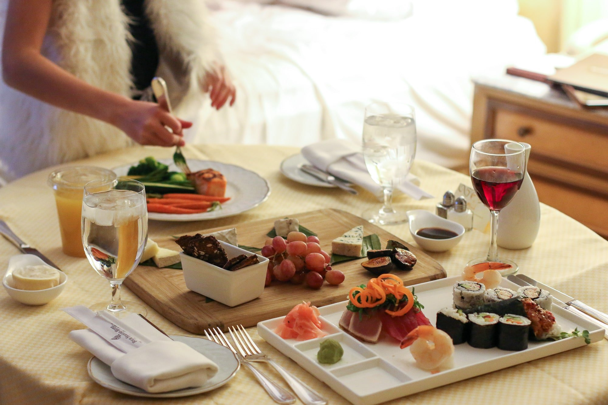 In-room dining tray with a cheese plate, sushi, seared ahi and more on top.