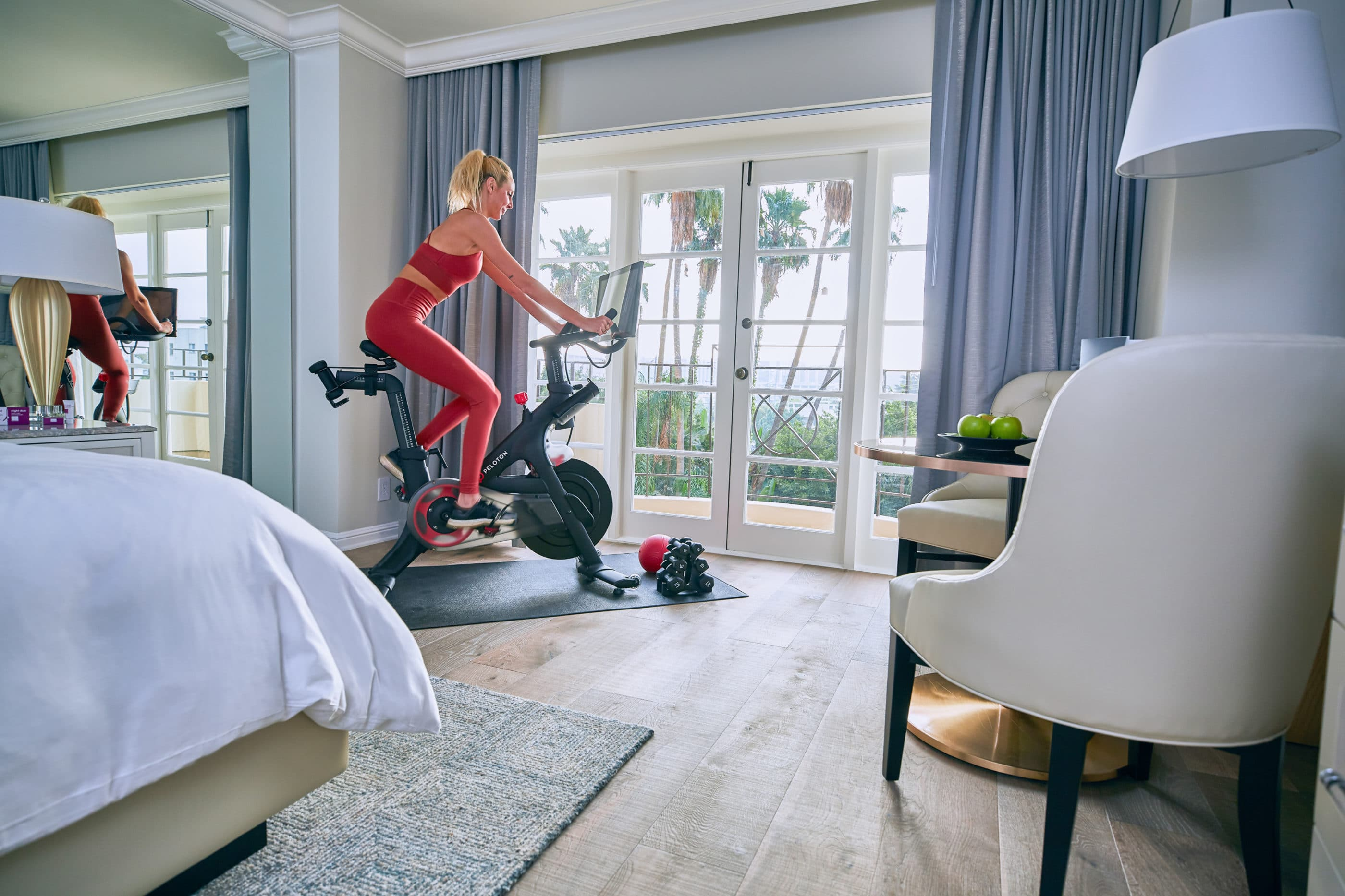 A woman rides a stationary bike in her room at Four Seasons Los Angeles
