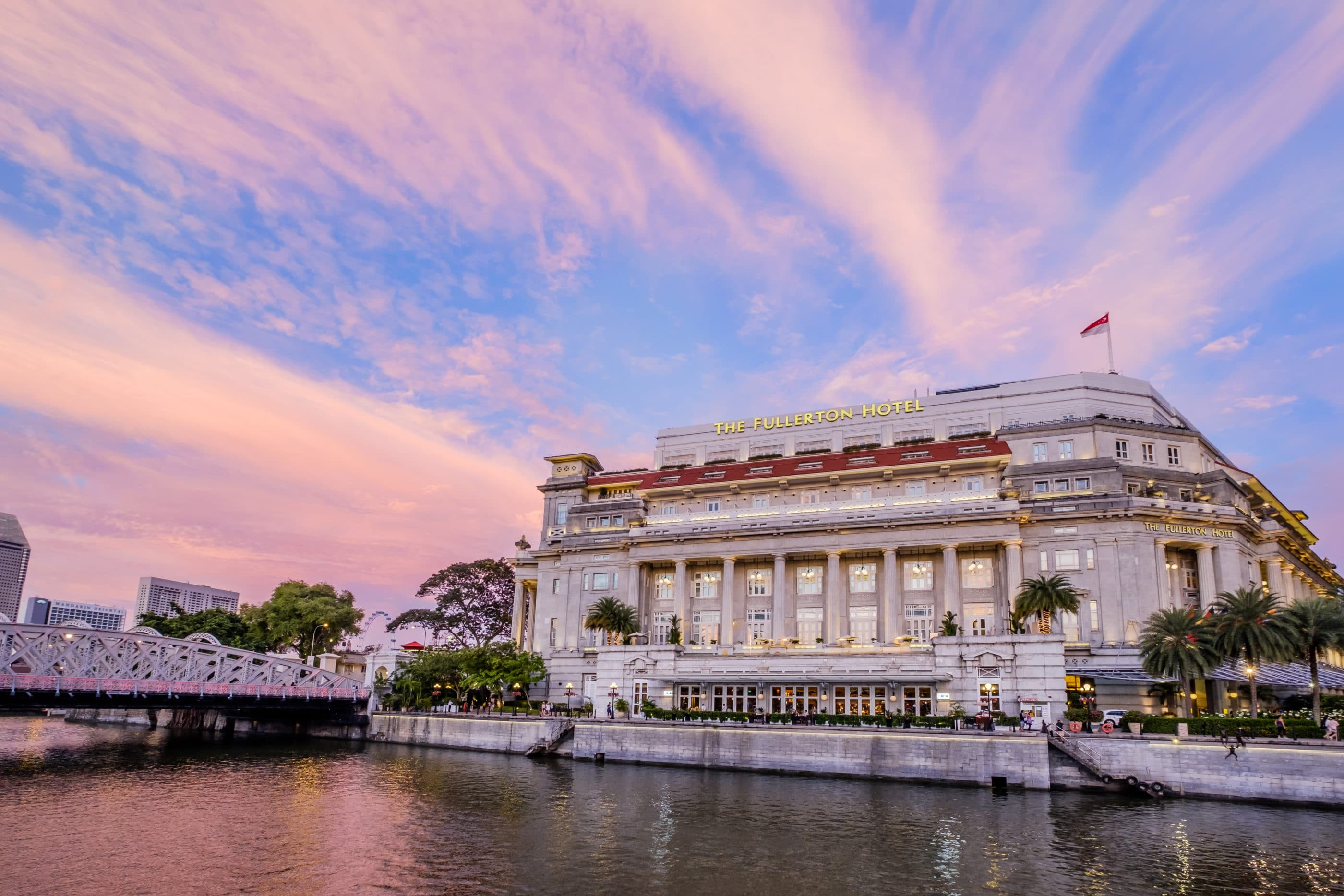 A view of The Fullerton Hotel's colonial exterior from across Marina Bay at sunset.
