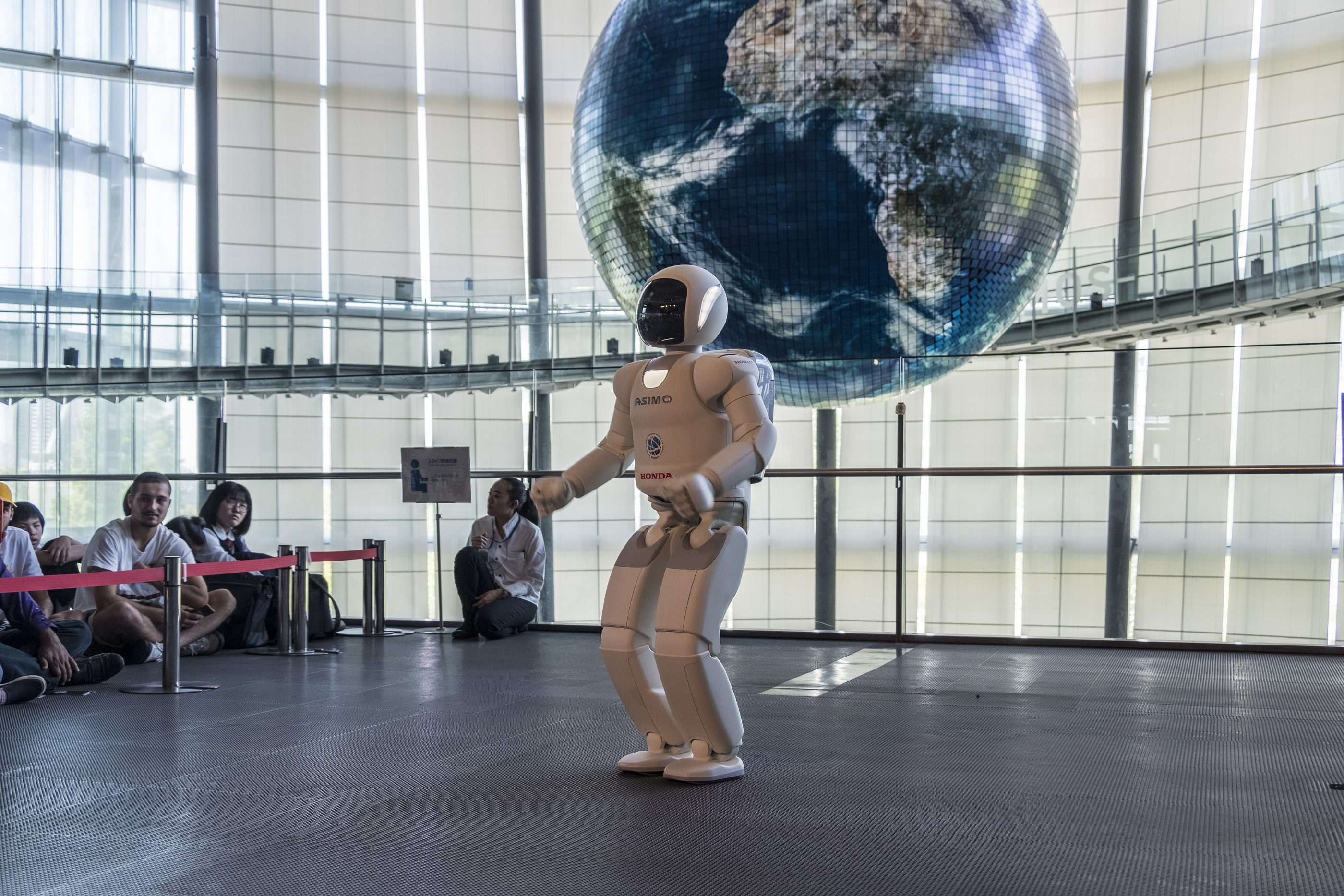 A robot demonstration next to the famous globe inside Miraikan museum in Tokyo.