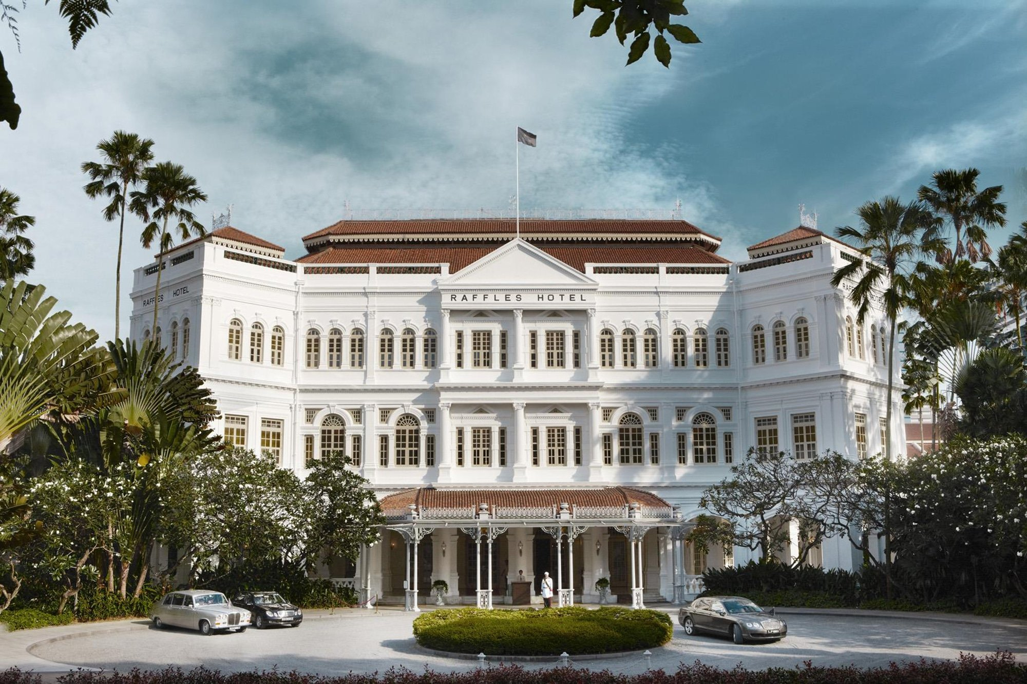 Colonial exterior of the famous Raffles Singapore Hotel. The famous doormen are standing in front.