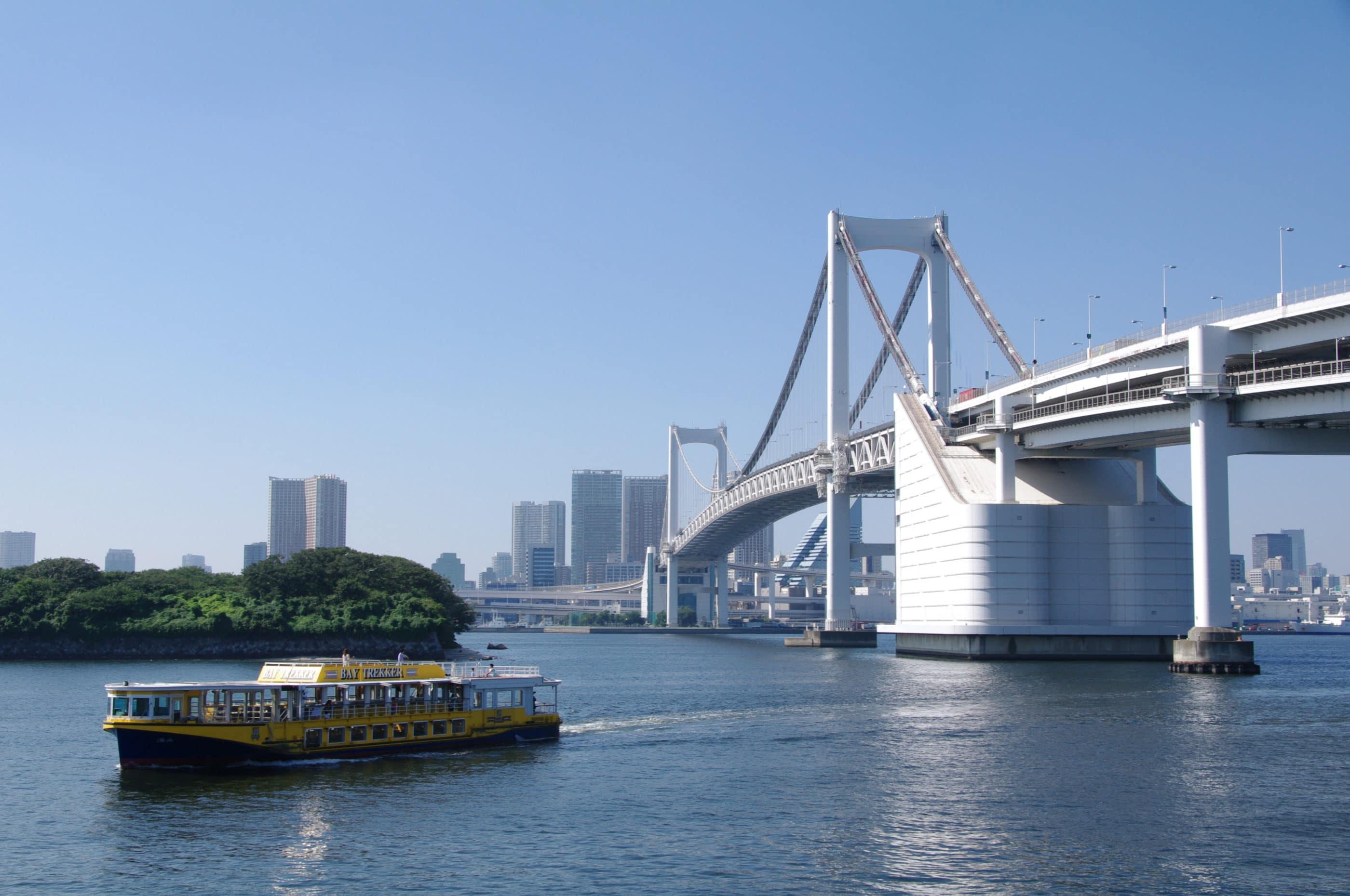 A tour boat on the water near the Rainbow Bridge to Odaiba island.