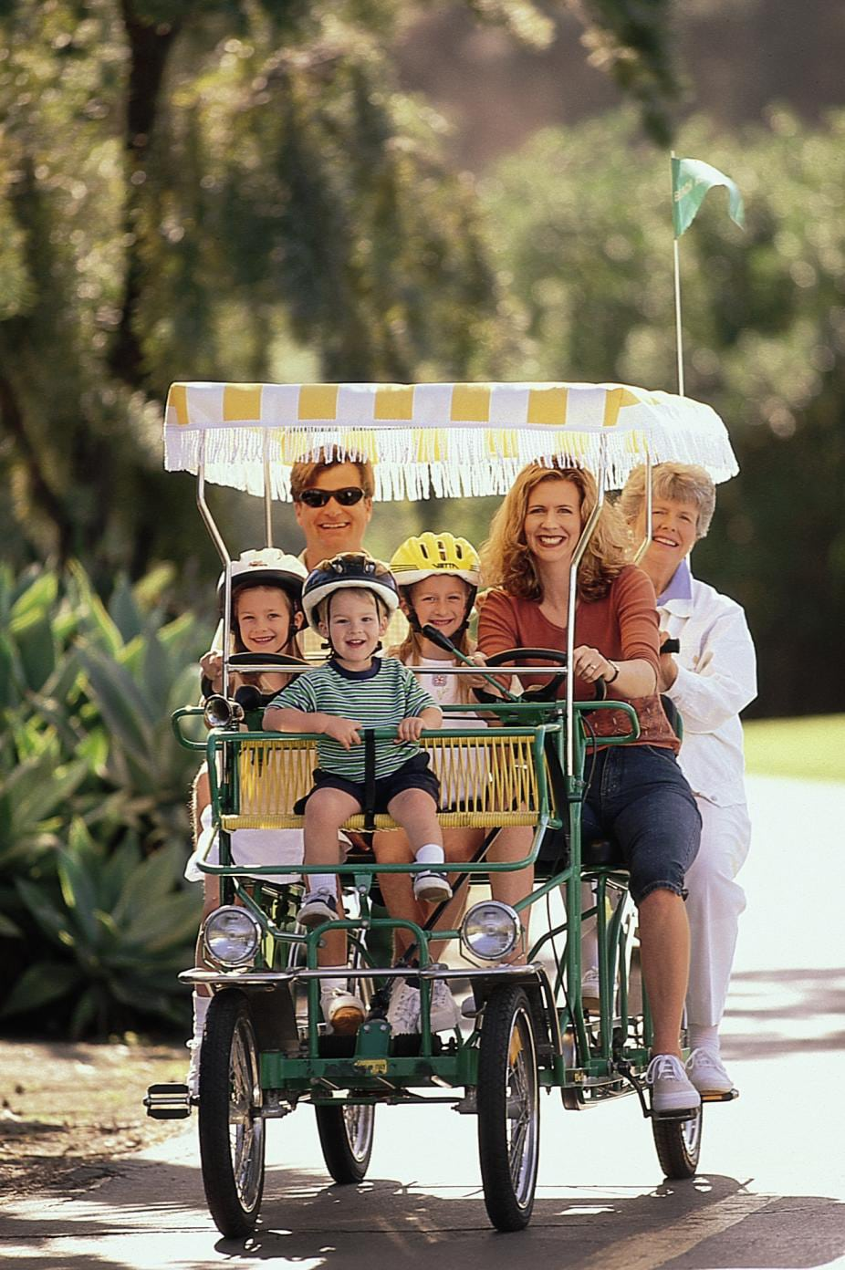 A multigenerational family riding a surrey bike down a sidewalk in Santa Barbara.