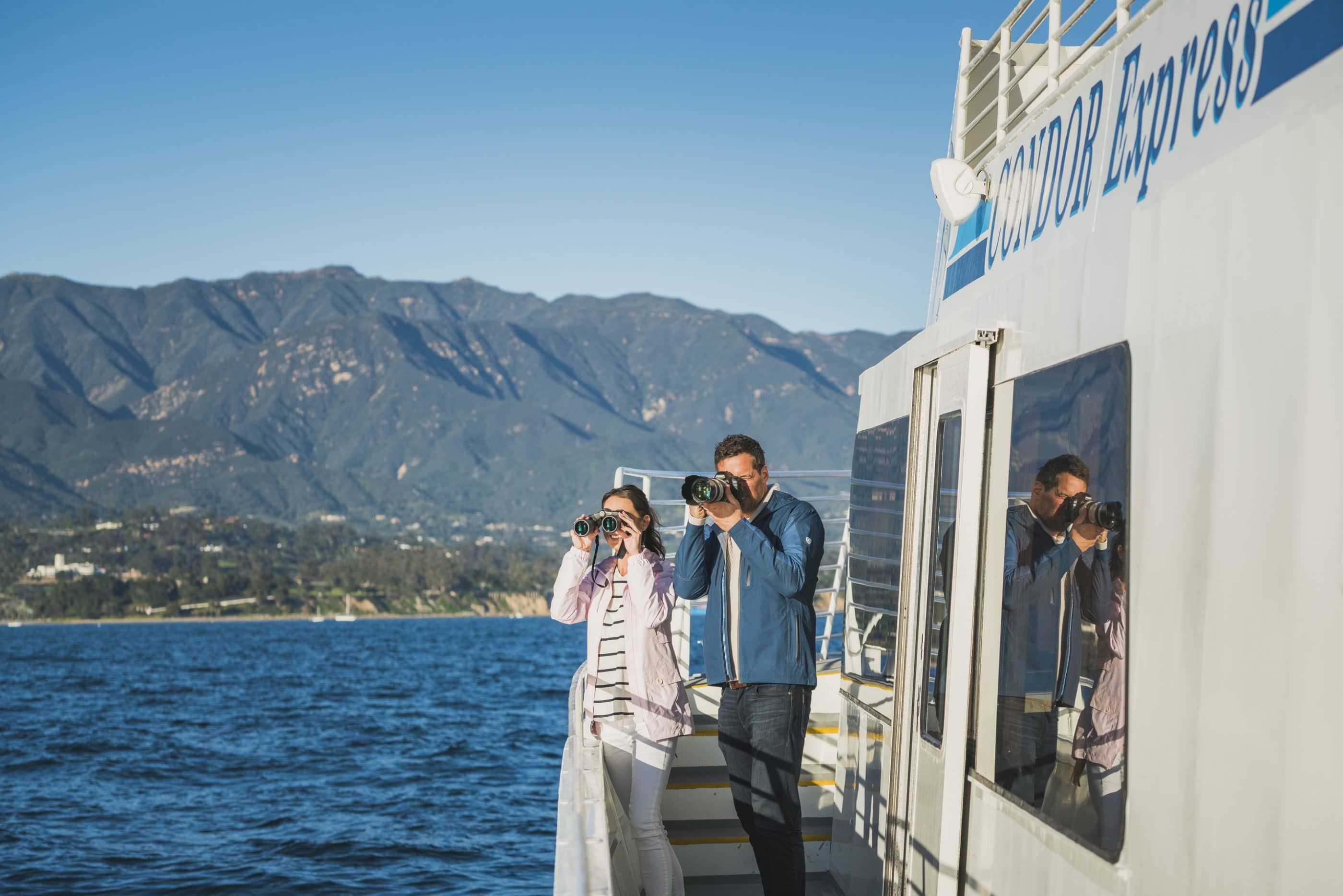 A couple with binoculars and a camera searching for whales on a boat near Santa Barbara.