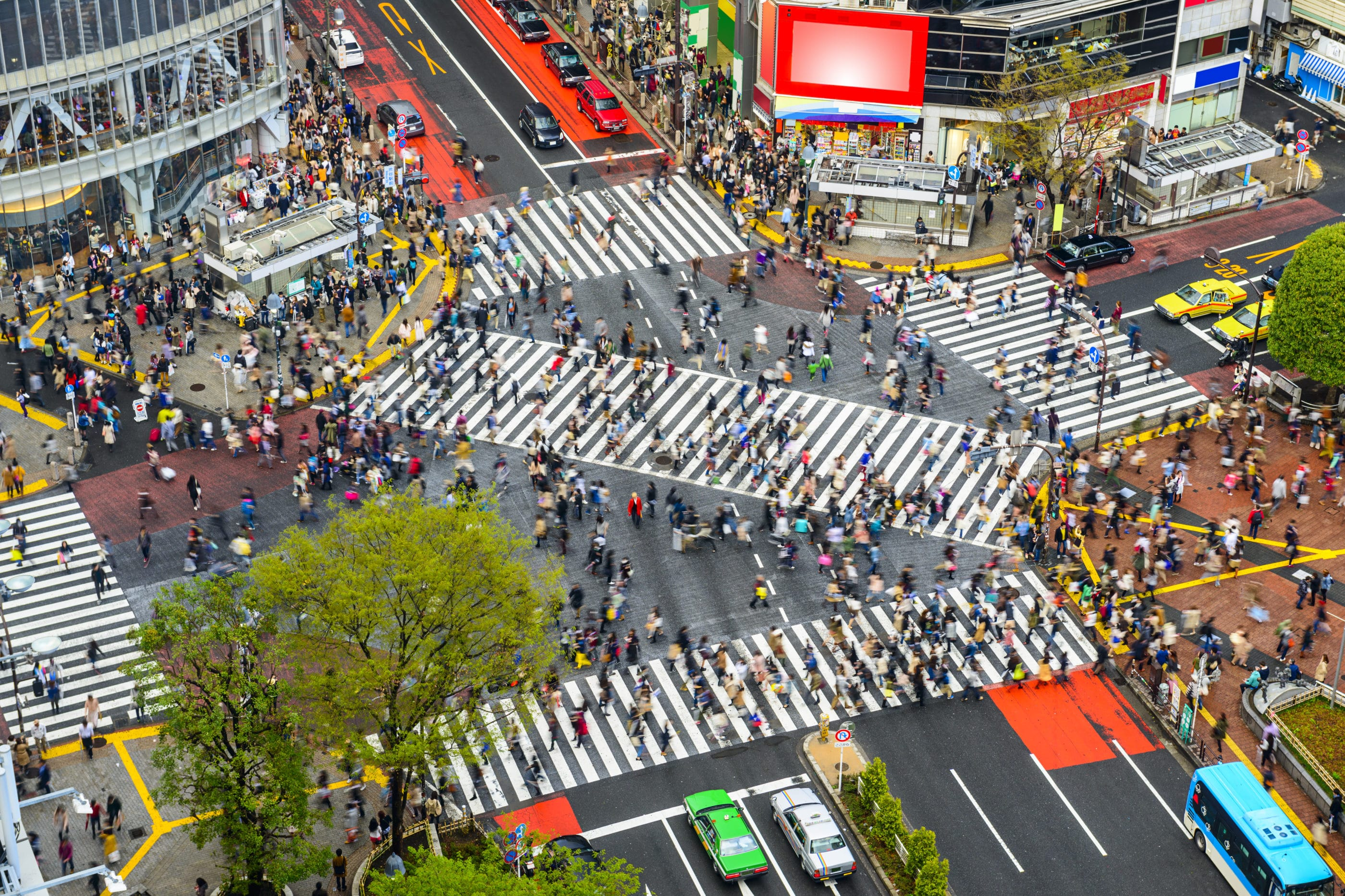An overhead view of people on the crosswalks of the Shibuya Crossing with traffic stopped in all directions.