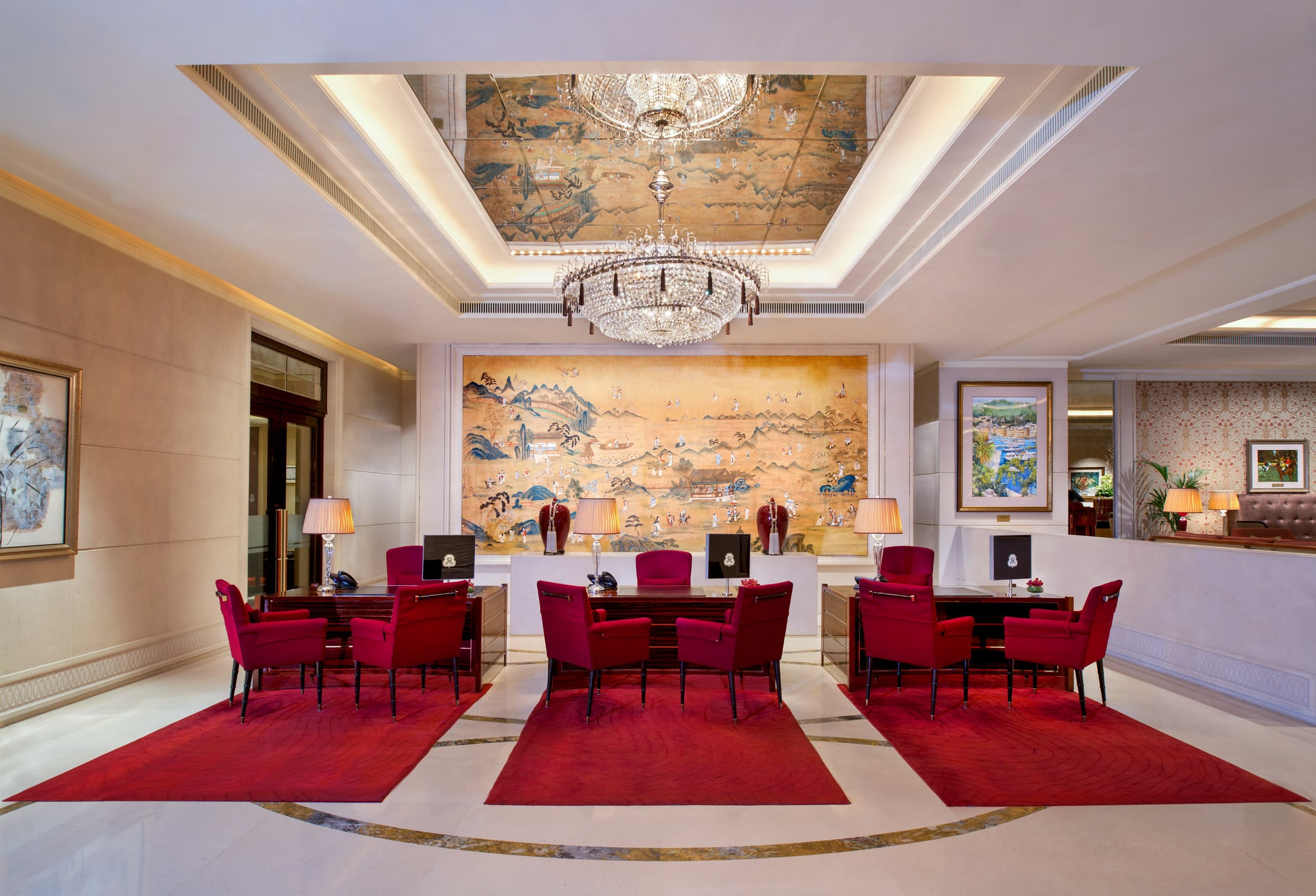 The lobby at St. Regis has deep red velvet chairs and rugs in addition to a gold Asian painting and crystal chandelier.