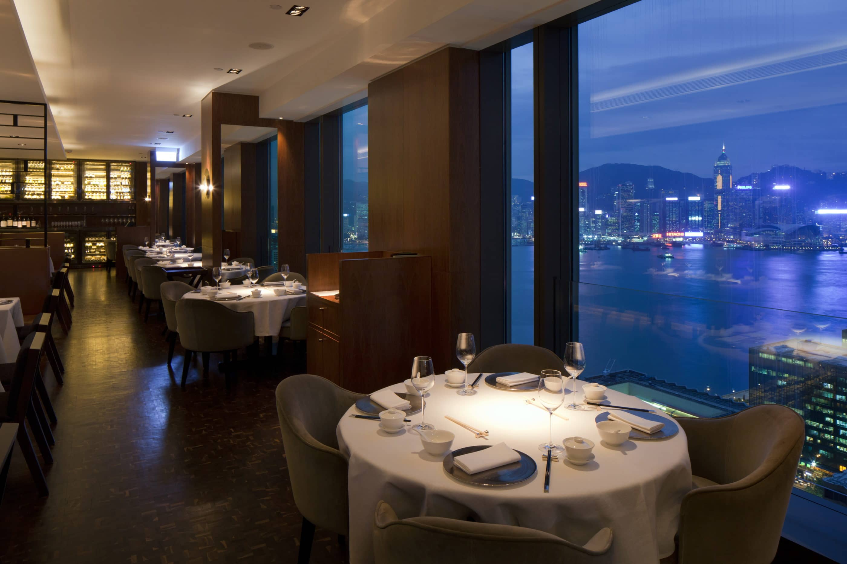 Tables near the windows at Above  & Beyond with nighttime panoramic harbour views.
