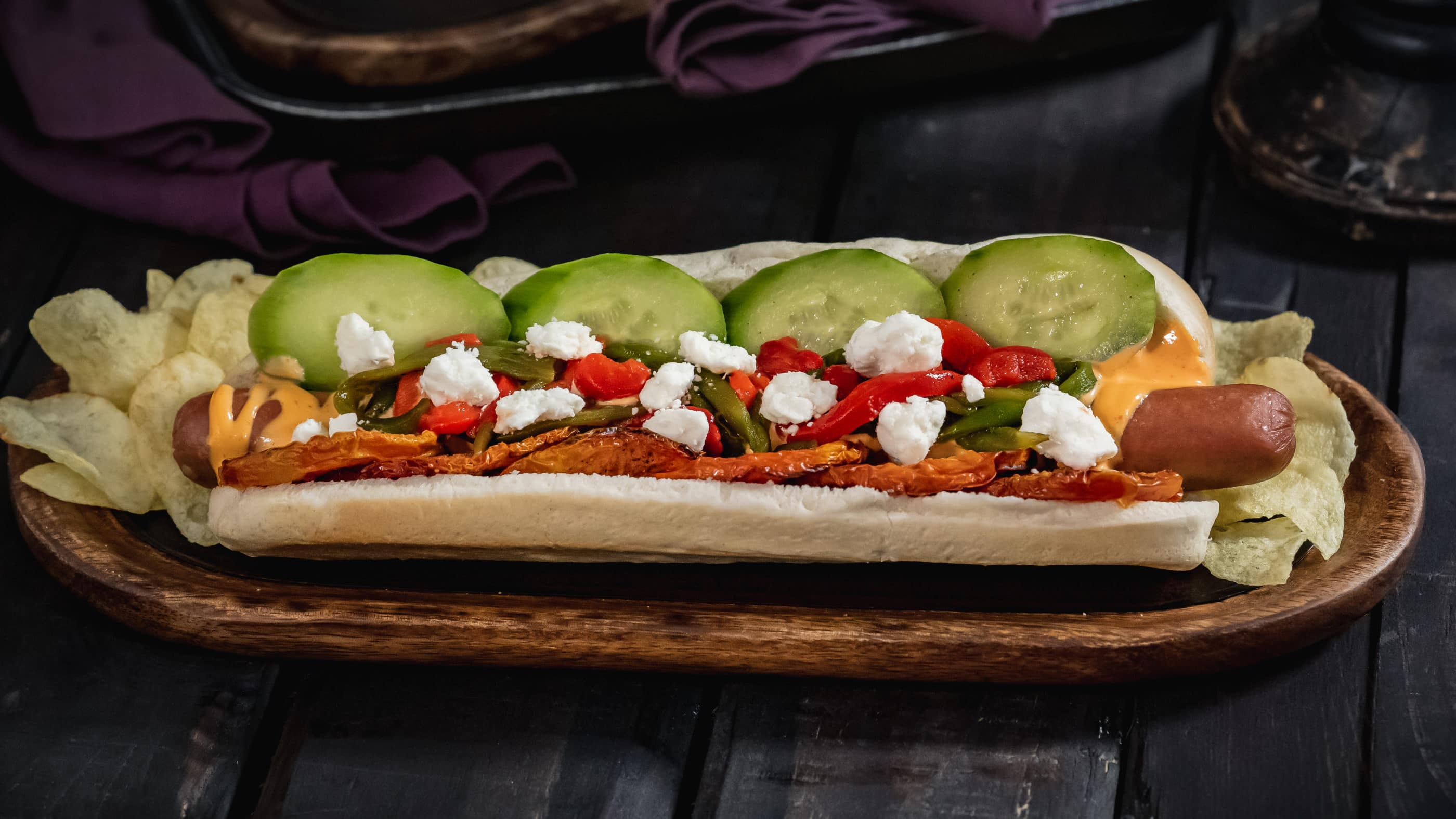 Hades-inspired hot dog with neatly-placed toppings on a wood board.