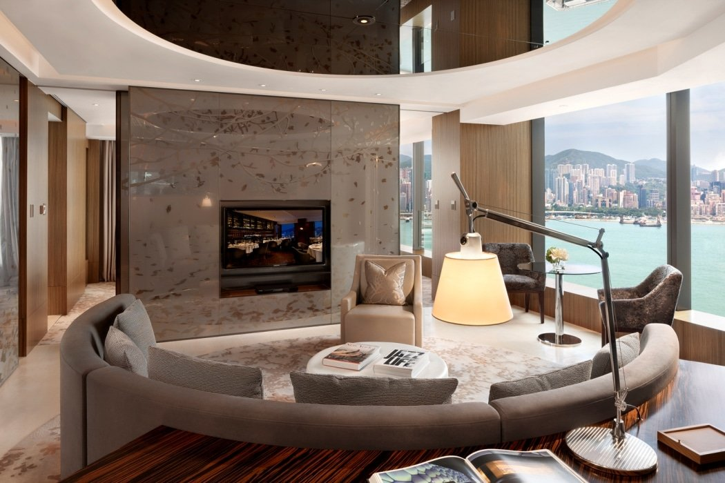 The living room with rounded sofa and Victoria Harbour views of a Club 80 Harbour Suite.