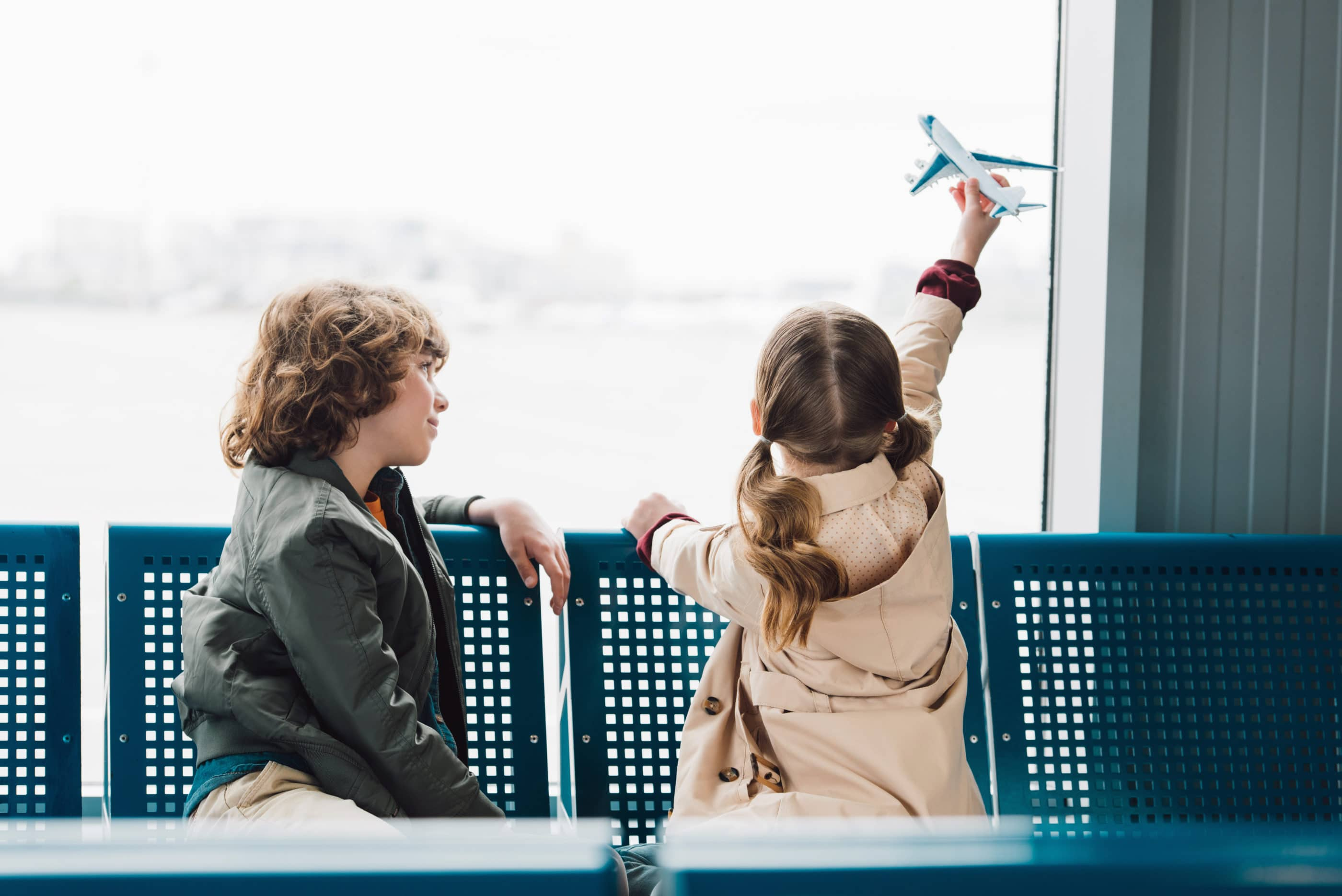 Travel with kids: A little girl flies a toy plane in her hand while a boy waits next to her in the airport.