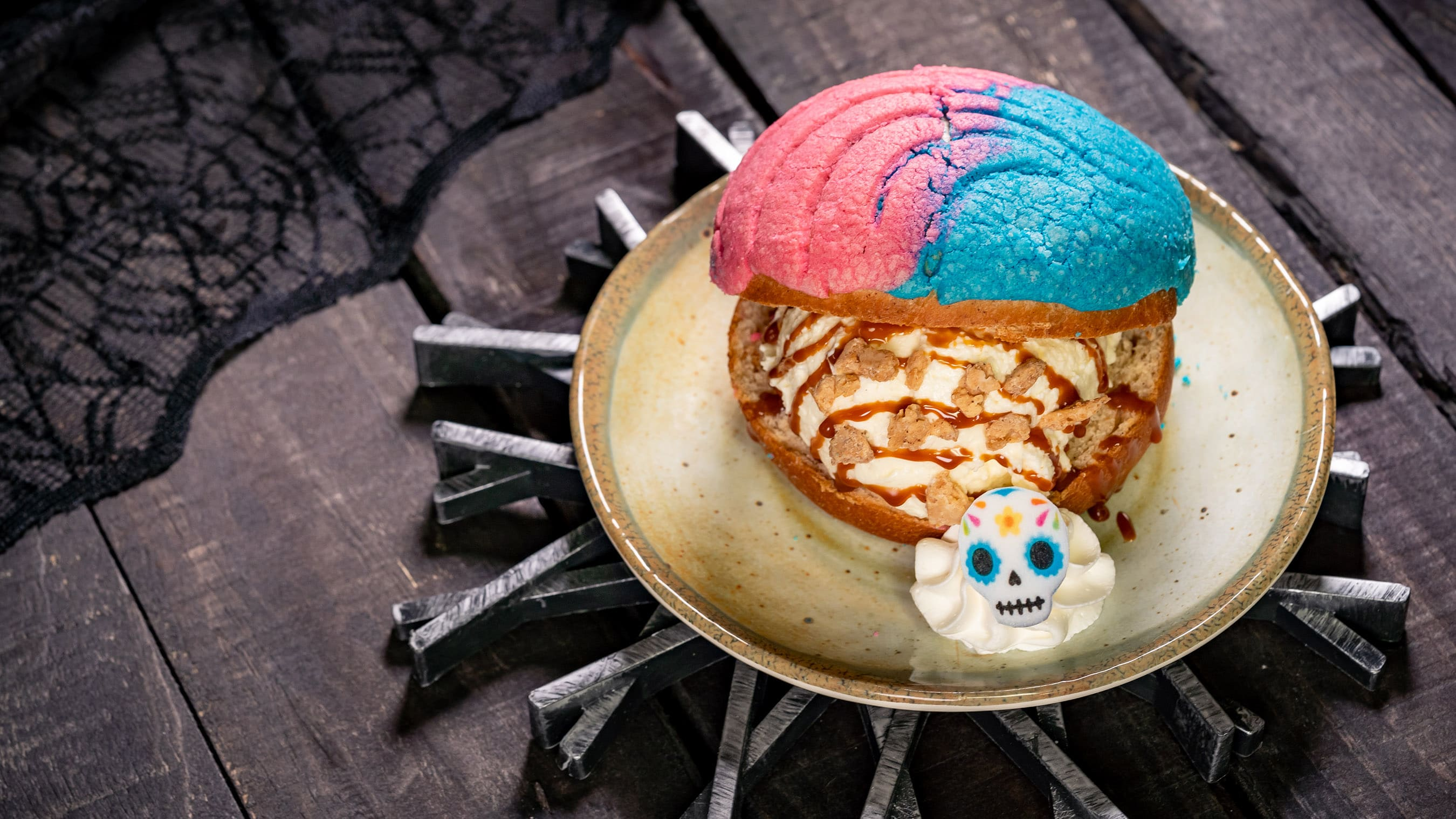 Pan Dulce Ice Cream sandwich on a place with a dollop of cream topped with a candy skull.