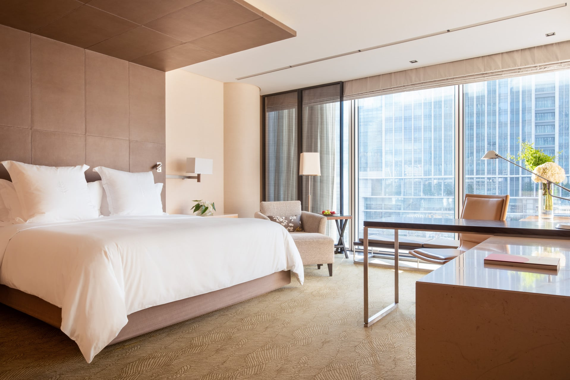The interior of a Deluxe King room looking out toward the city view.