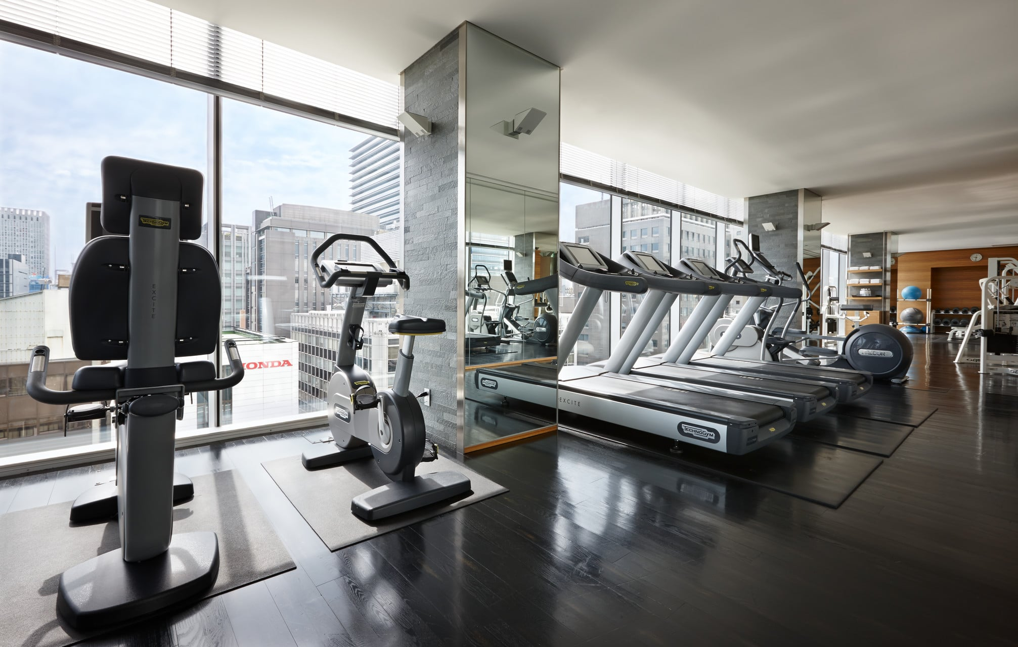Cardio machines overlooking floor-to-ceiling windows with city views in the fitness center.