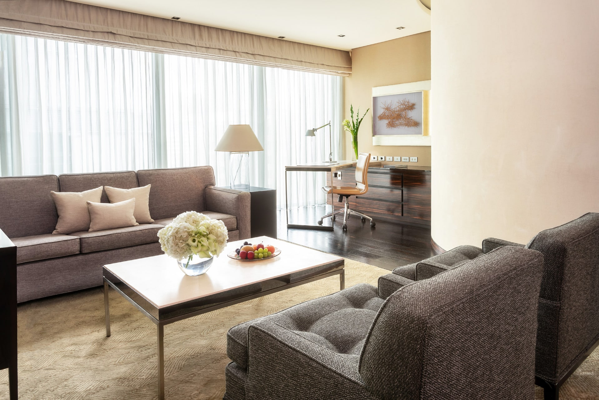 The seating and desk area of the One-Bedroom Suite at Four Seasons Hotel Tokyo at Marunouchi features neutral tones.