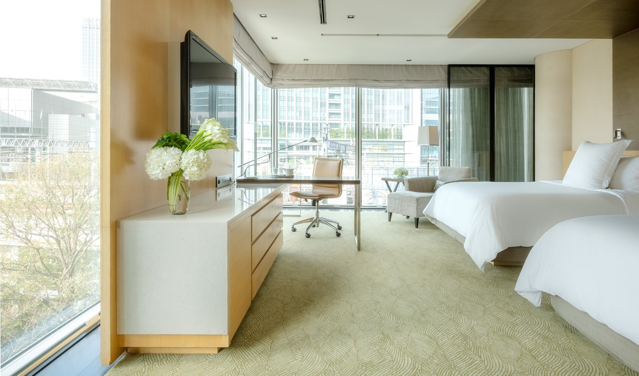 The interior of a Premier Twin corner room features lots of light through the multiple windows, white sheets and a neutral toned desk and seating area.