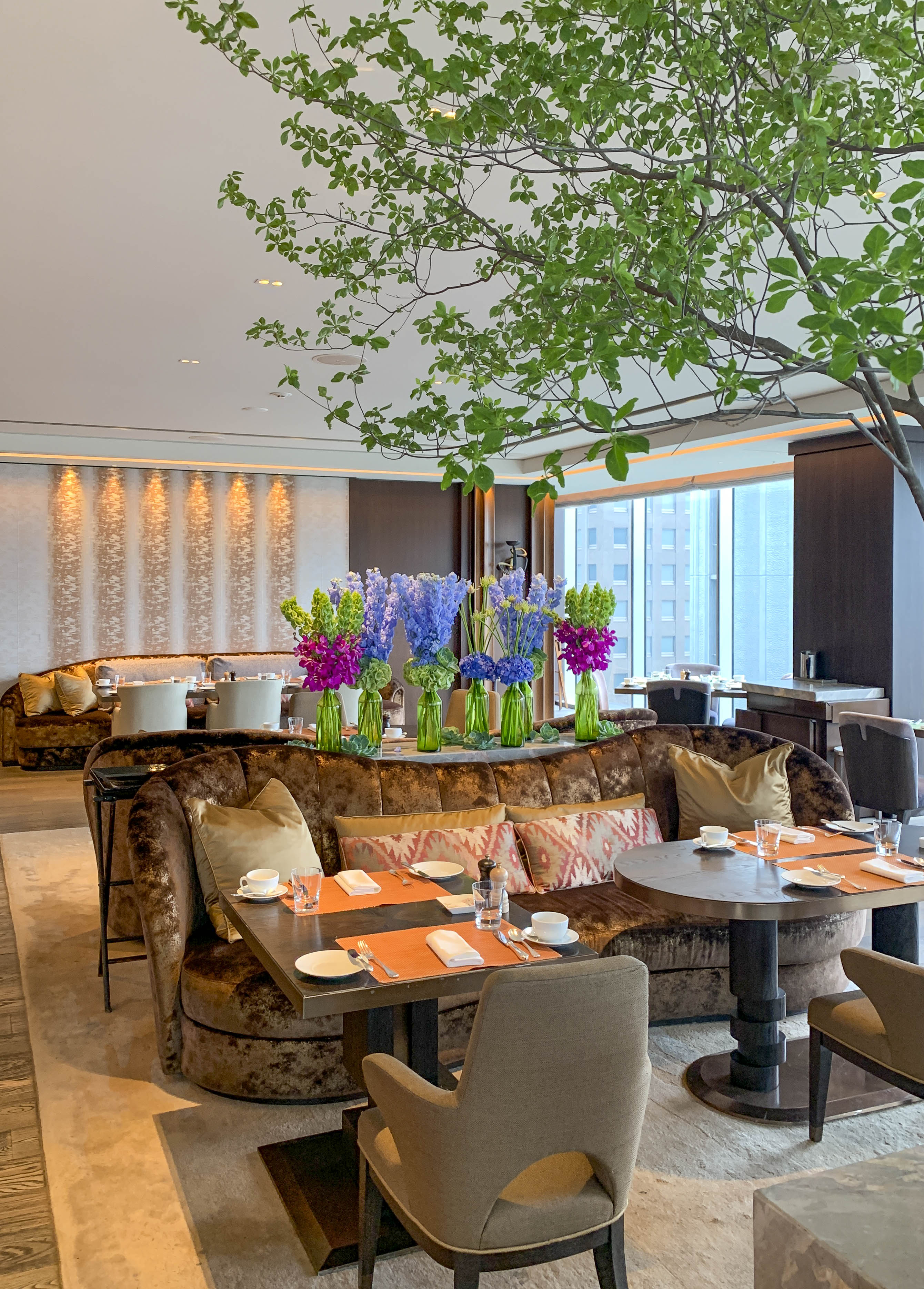 Plush seating, hydrangea flower arrangements and tree inside Motif in the early morning.