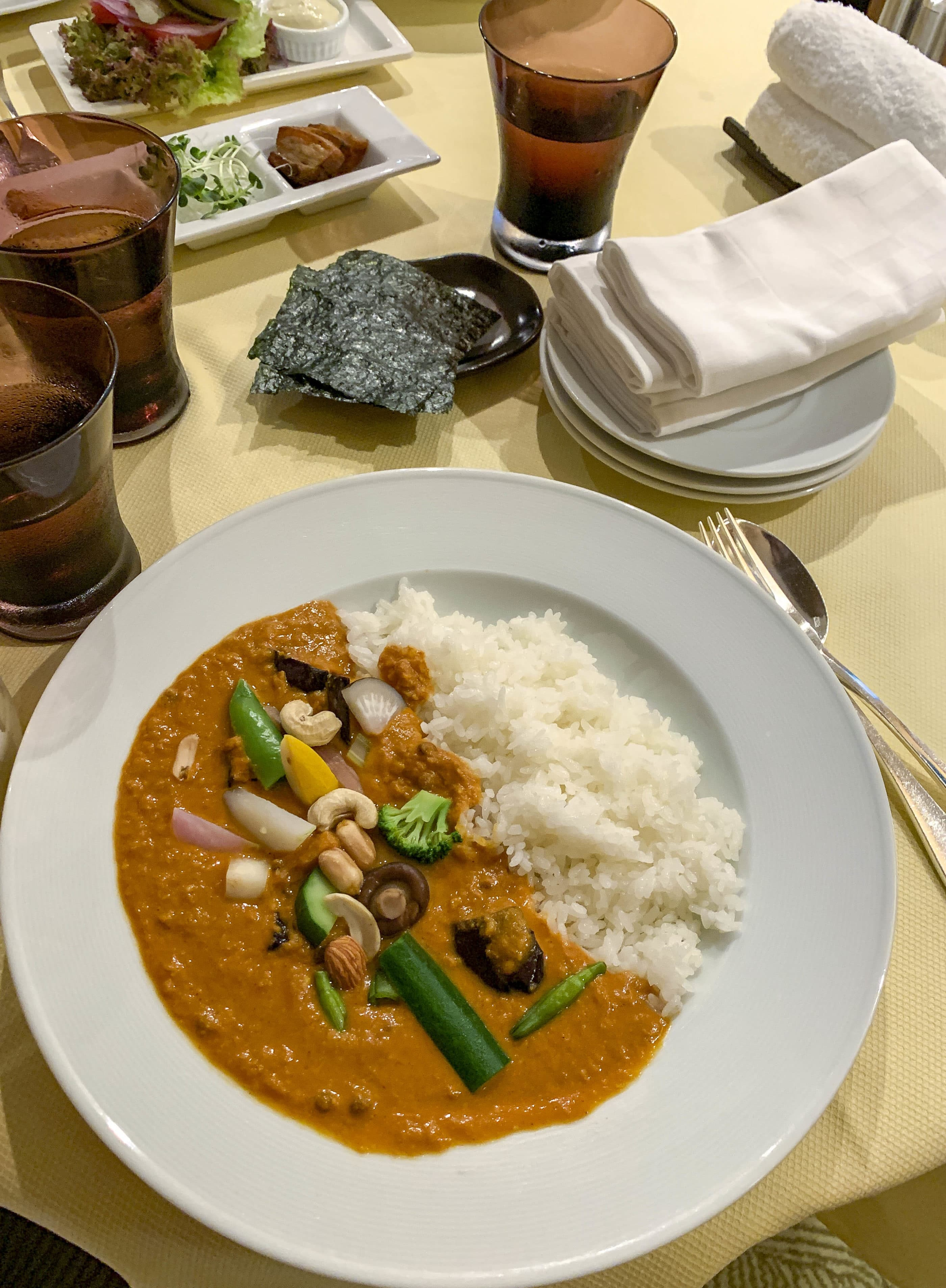 A plate of Japanese curry and rice with perfectly-placed steamed vegetables on top of a room service cart.