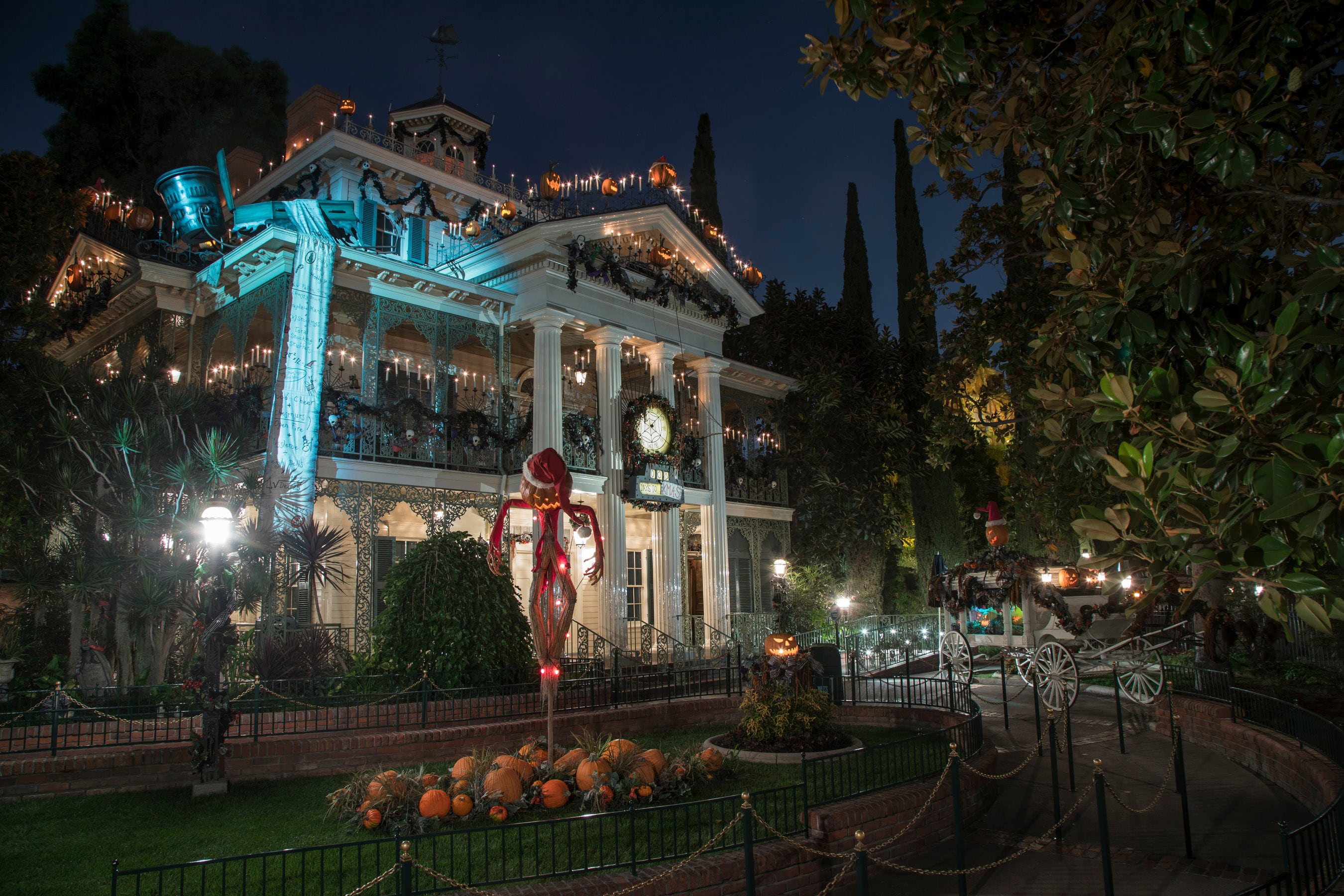 Jack Skellington poses in front of Haunted Mansion Holiday.