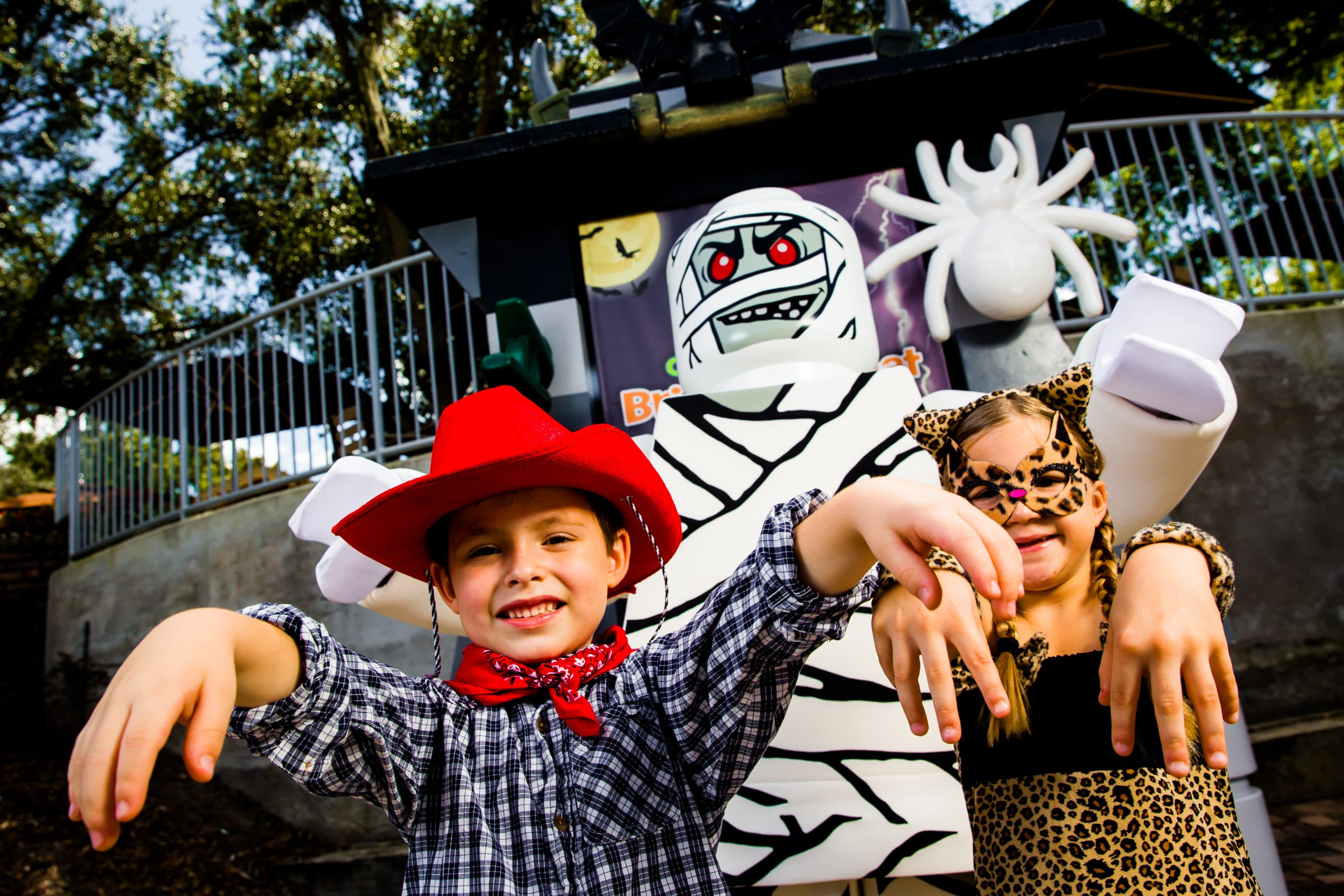 Two children in Halloween costumes pose next to a life-size LEGO mini figure mummy at Brick-or-Treat