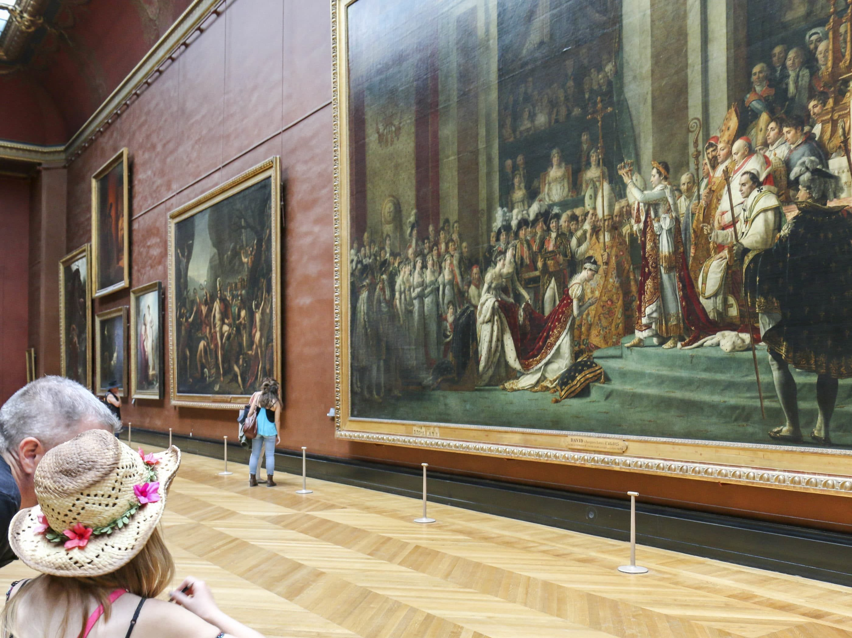 My husband explaining to my daughter the significance of The Coronation of Napoleon by Jacques-Louis David in front of the massive painting.