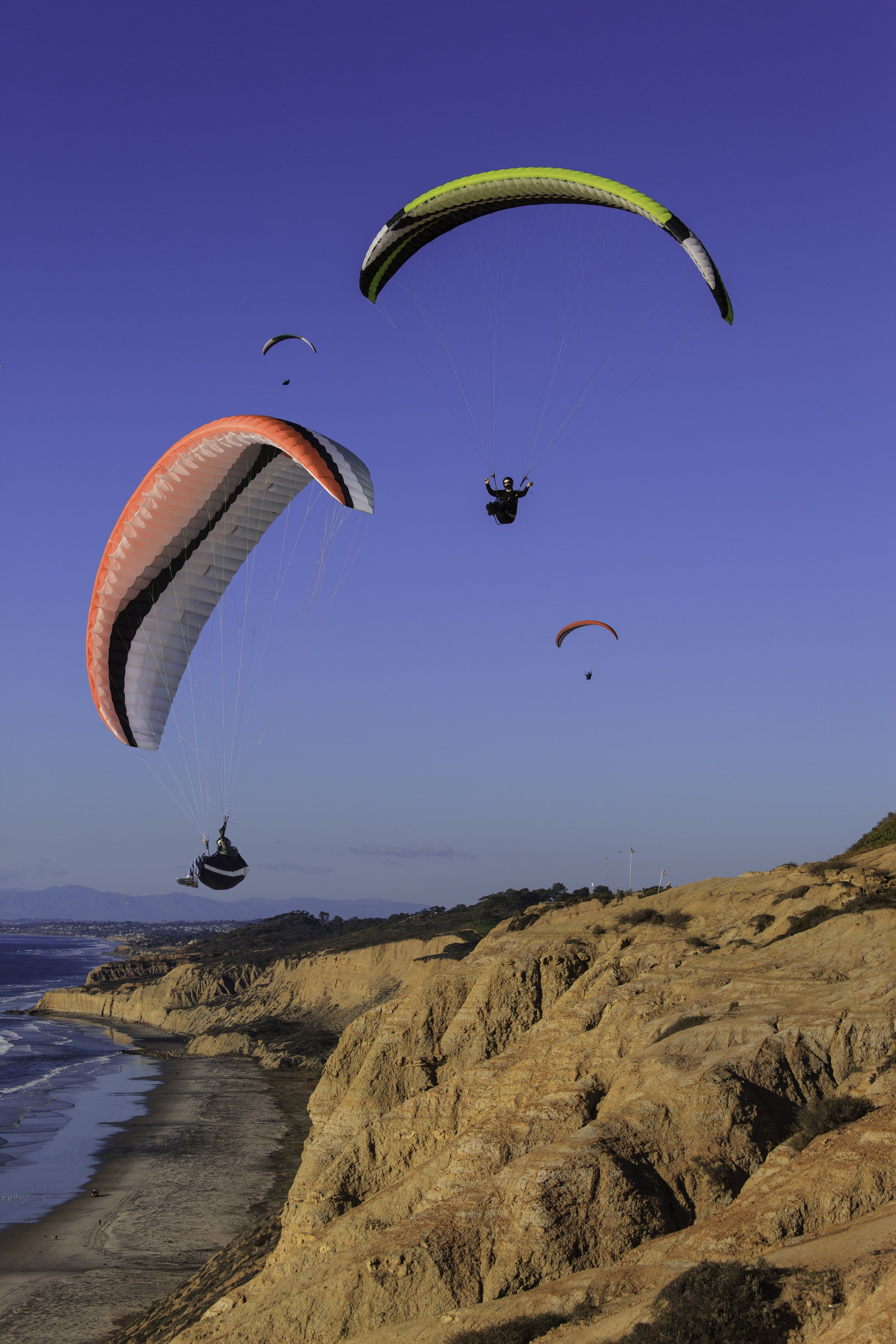 Gliders with colorful parachutes against blue sky and over the bluffs at Torrey Pines Gliderport.