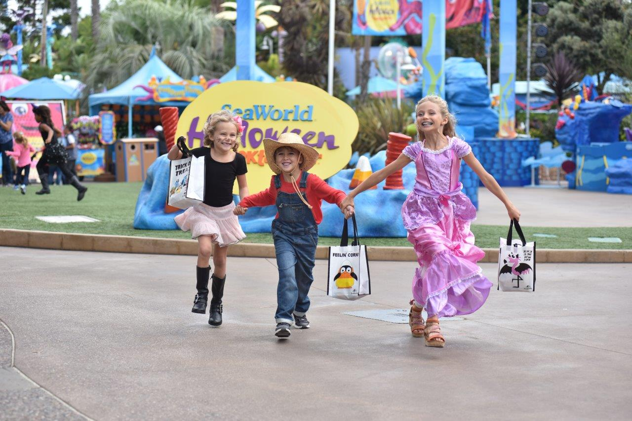 Kids in costume holding trick-or-treat bags at SeaWorld San Diego.