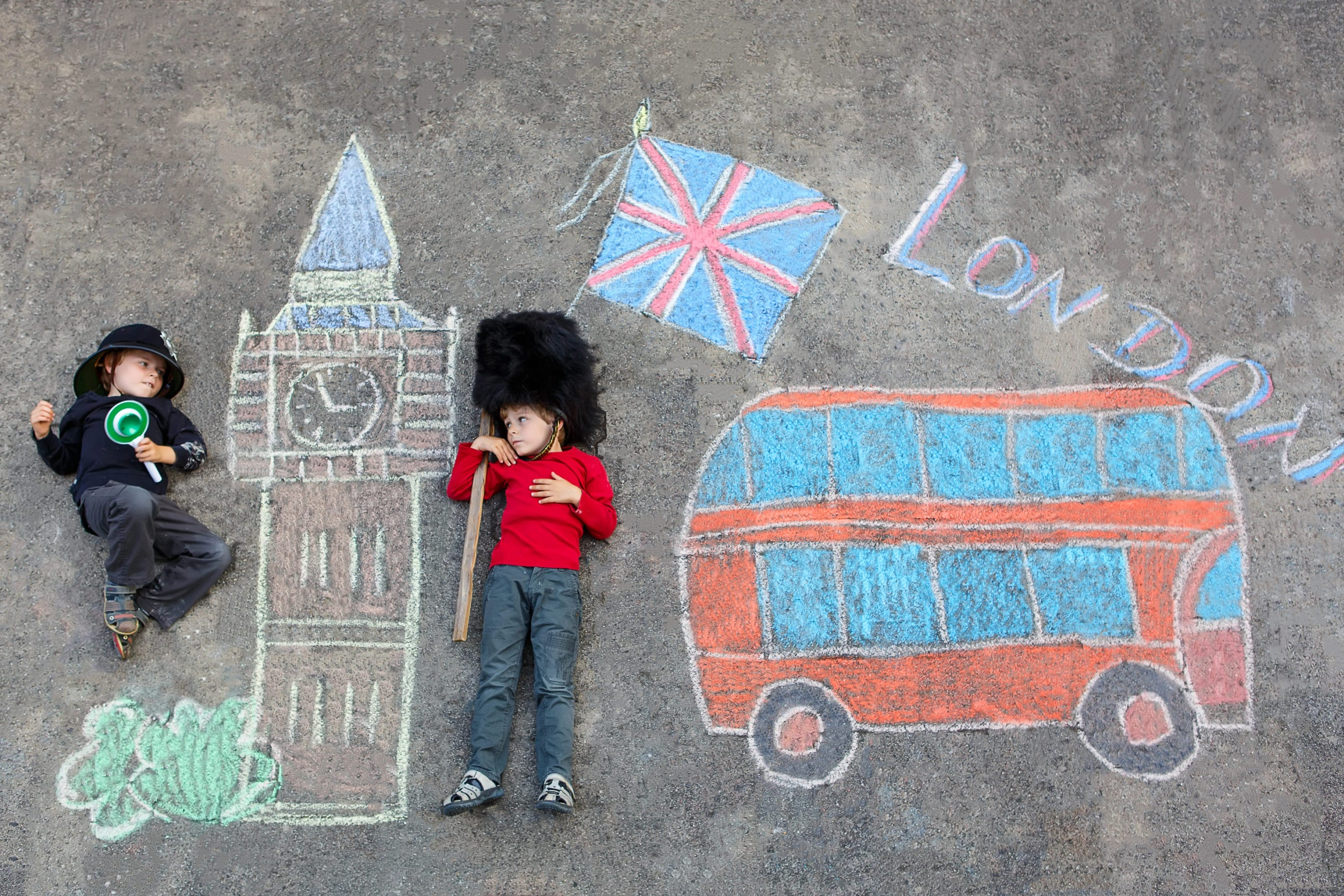 Two funny little friends boys in british queen's guard soldier and policeman uniform having fun with London picture drawing with colorful chalks. With Big Ben, Union Jack and red bus.