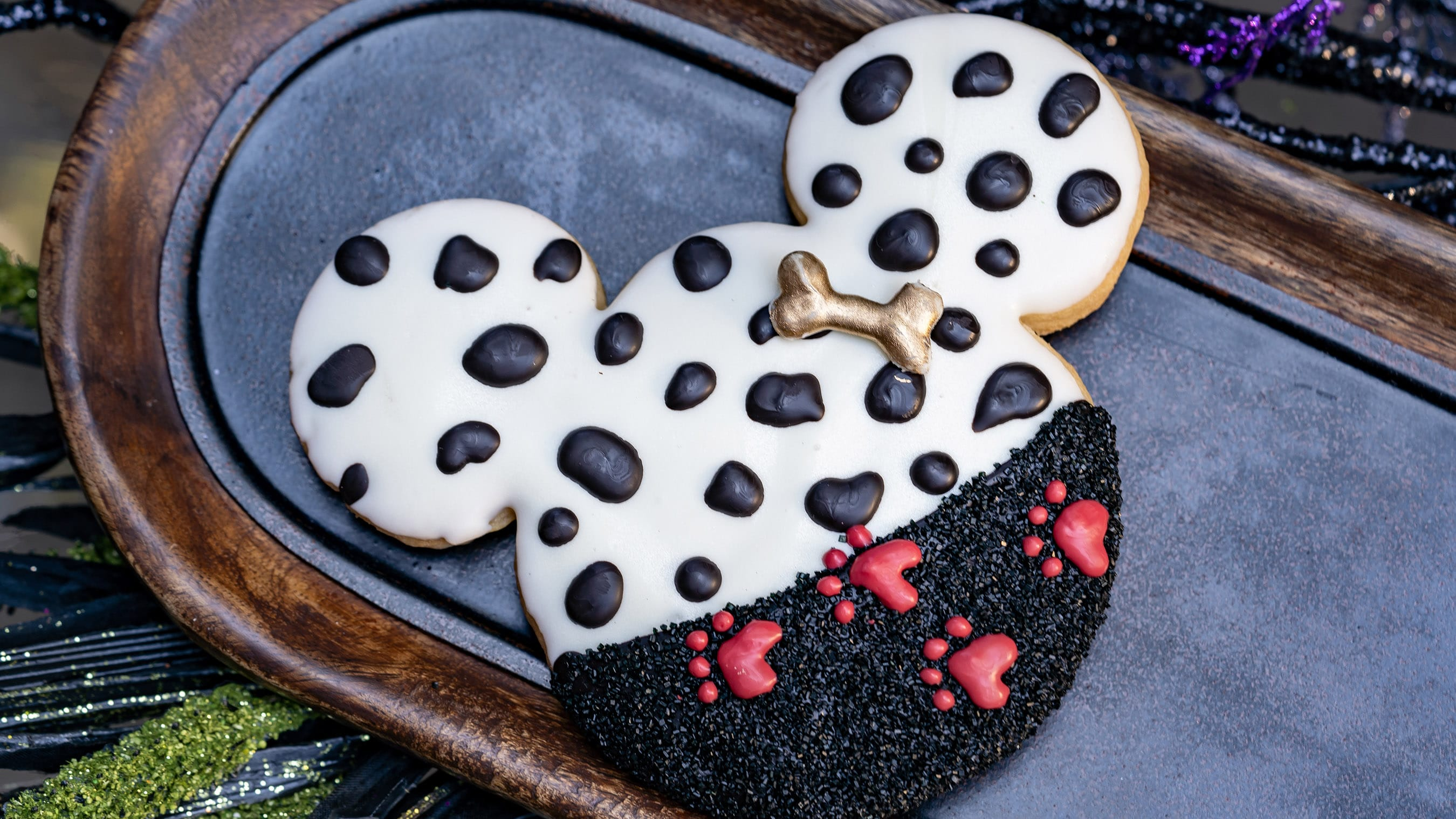 A cookie shaped like a Mickey head with dalmatian spots and red footprints.