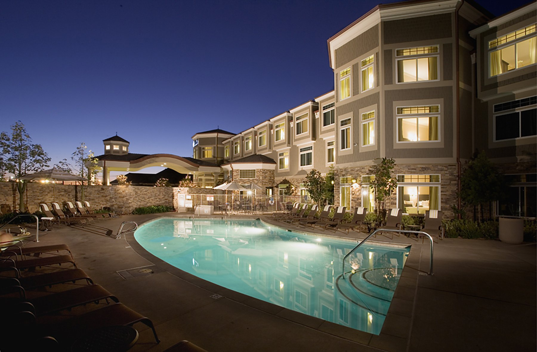 The pool deck lit up at night with the three-story hotel building behind it.