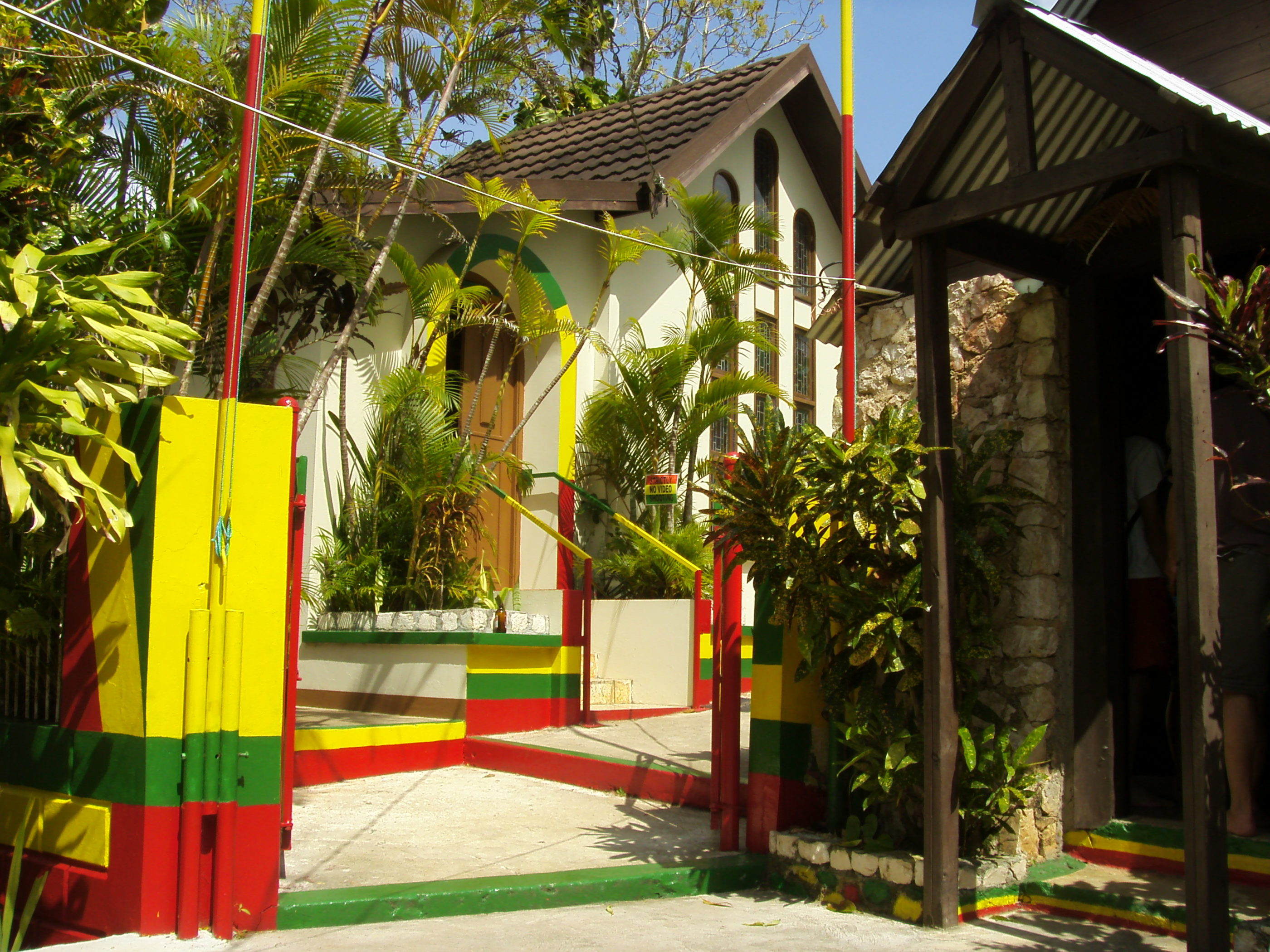 The exterior, with red, yellow and green stripe accents on poles, stairs and gates, to the Bob Marley Mausoleum.