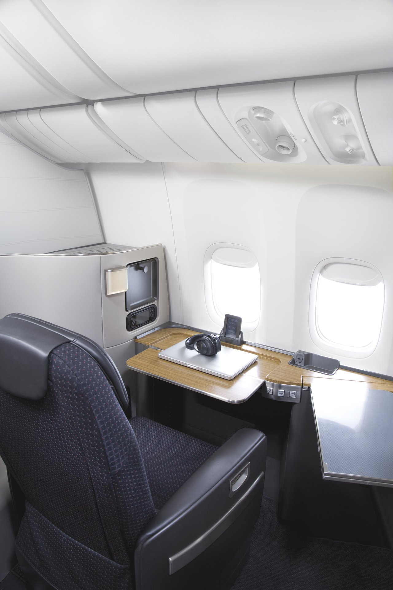 A first class chair on a Boeing 777 turned to face the window and desk in office mode.