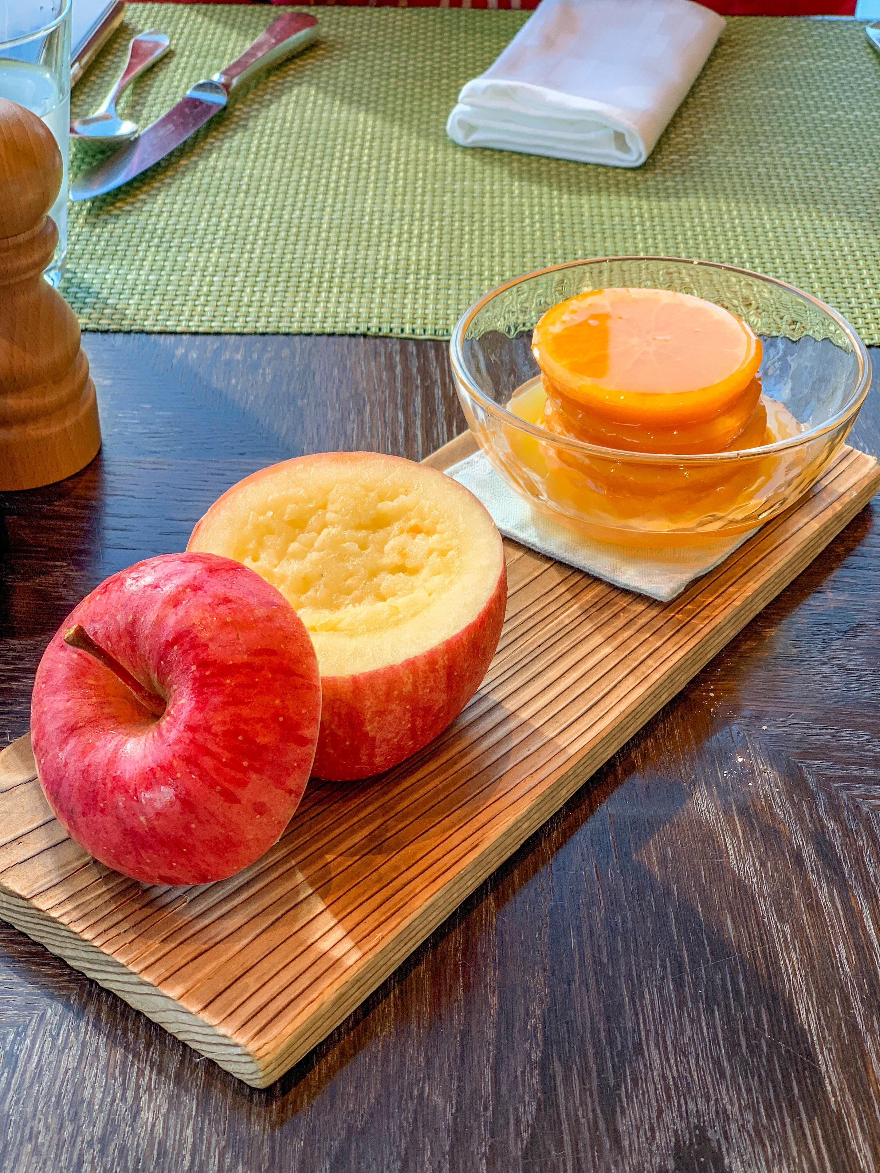 Complimentary apple compote and sweet oranges on a wood plank are given to guests at breakfast at Four Seasons Hotel Tokyo at Marunouchi.
