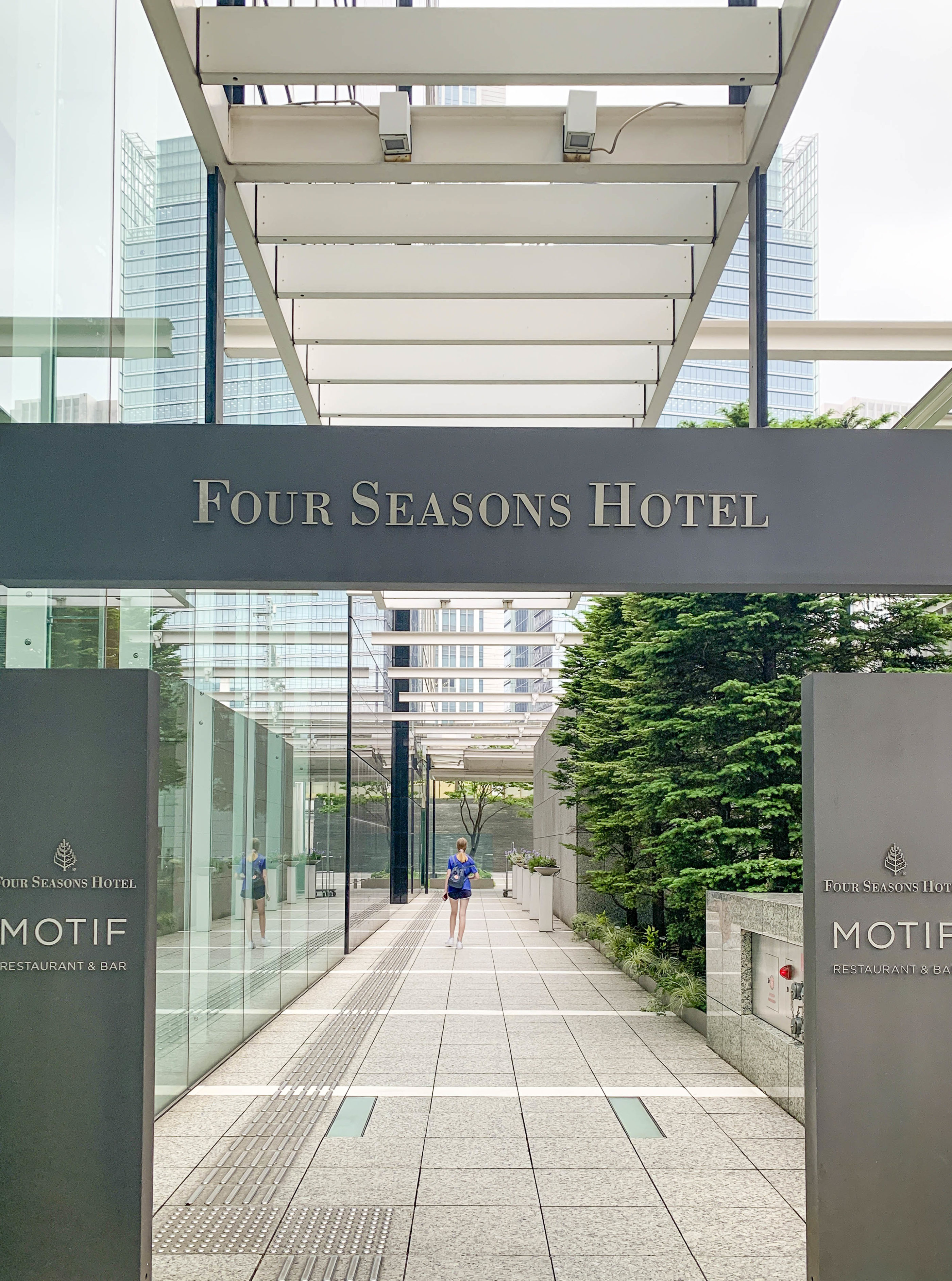 The street entrance to Four Seasons Hotel Tokyo at Marunouchi with a hotel sign.