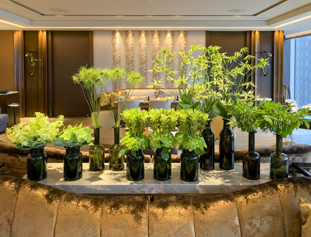 Multiple black vases full of various green flowers serve as the focal point of Motif restaurant.